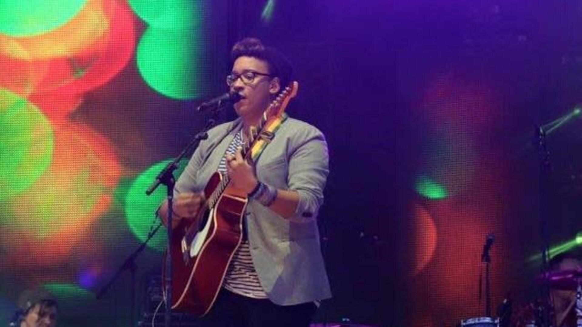 Un musicien est sur une scène et joue de la guitare.