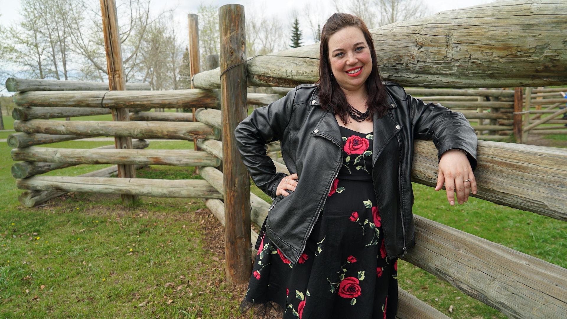 Une femme accotée à une clôture.