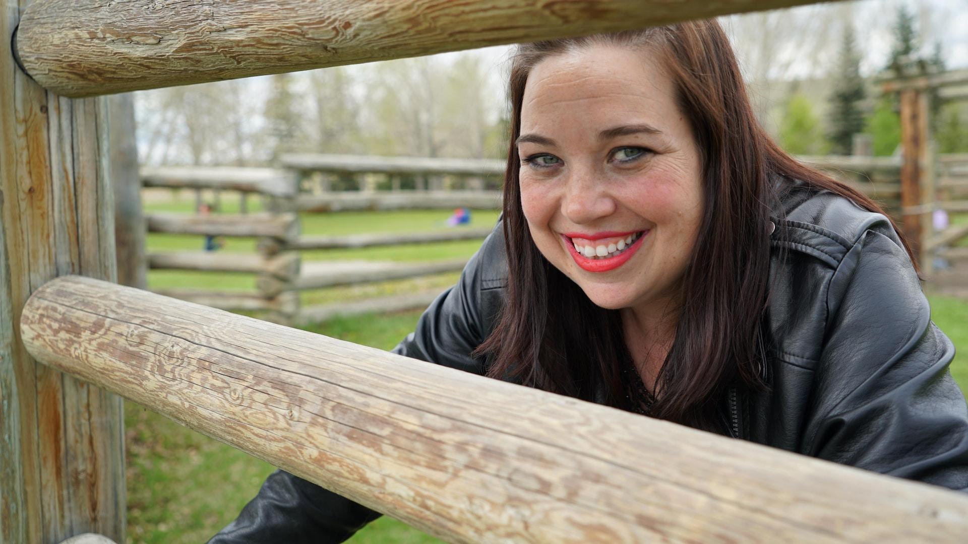 Une femme sourit derrière une clôture en bois.
