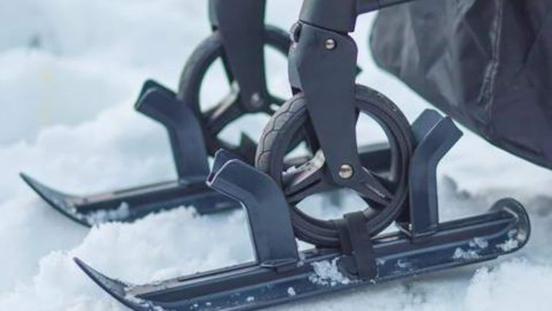 Plan rapproché de deux skis installés sur les roues avant d'une poussette. Il y a de la neige.