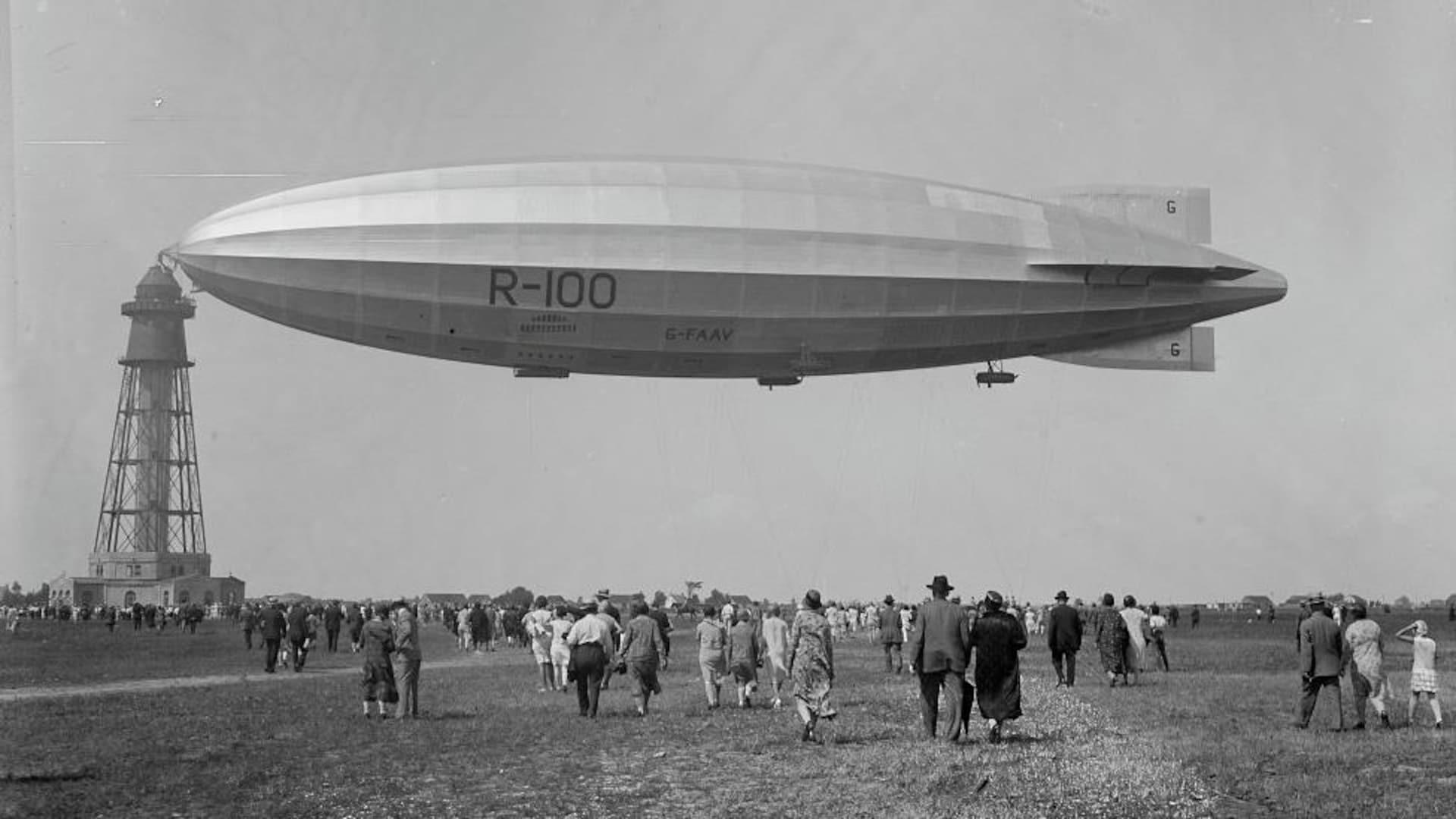 On voit une petite foule de gens dispersés se diriger vers le R-100. Le dirigeable semble suspendu dans les airs, bien ancré à son mât sous un ciel radieux.