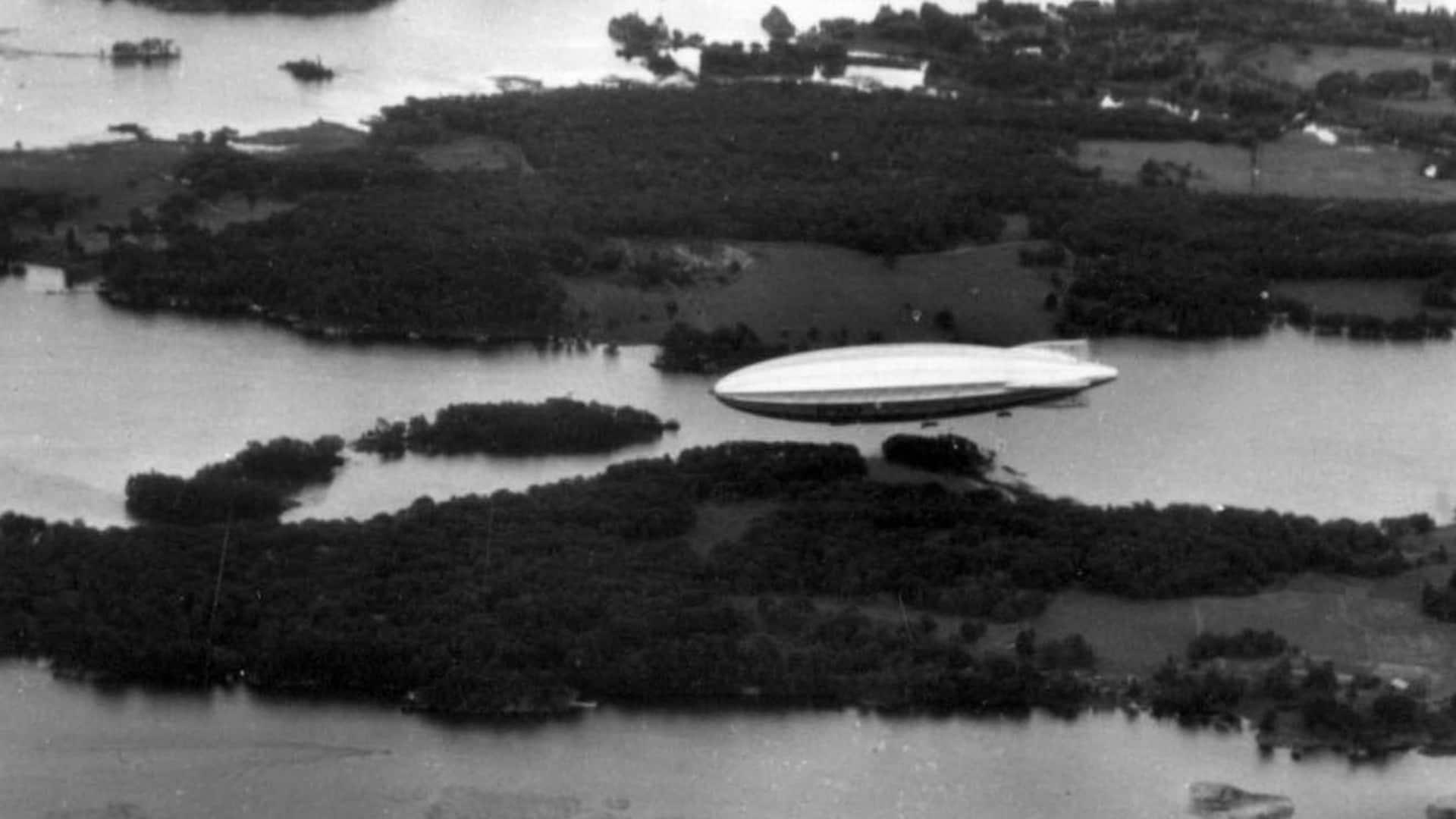 Le dirigeable survole une région d'îles et de lacs à basse altitude. La photo a visiblement été prise d'un avion qui l'accompagnait sur un bout de chemin.