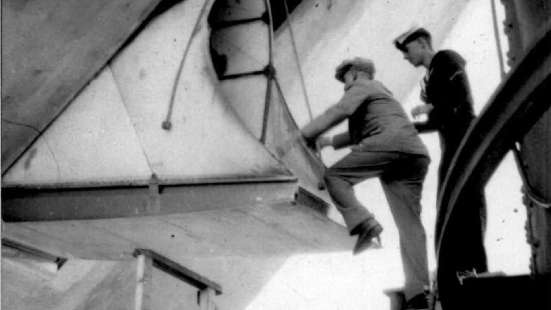 Un homme plutôt petit doit se faire assister d'un membre d'équipage pour entrer dans le dirigeable. Même l'escabeau installé sur la passerelle ne permet pas de combler le vide entre le mât et l'entrée du ballon.