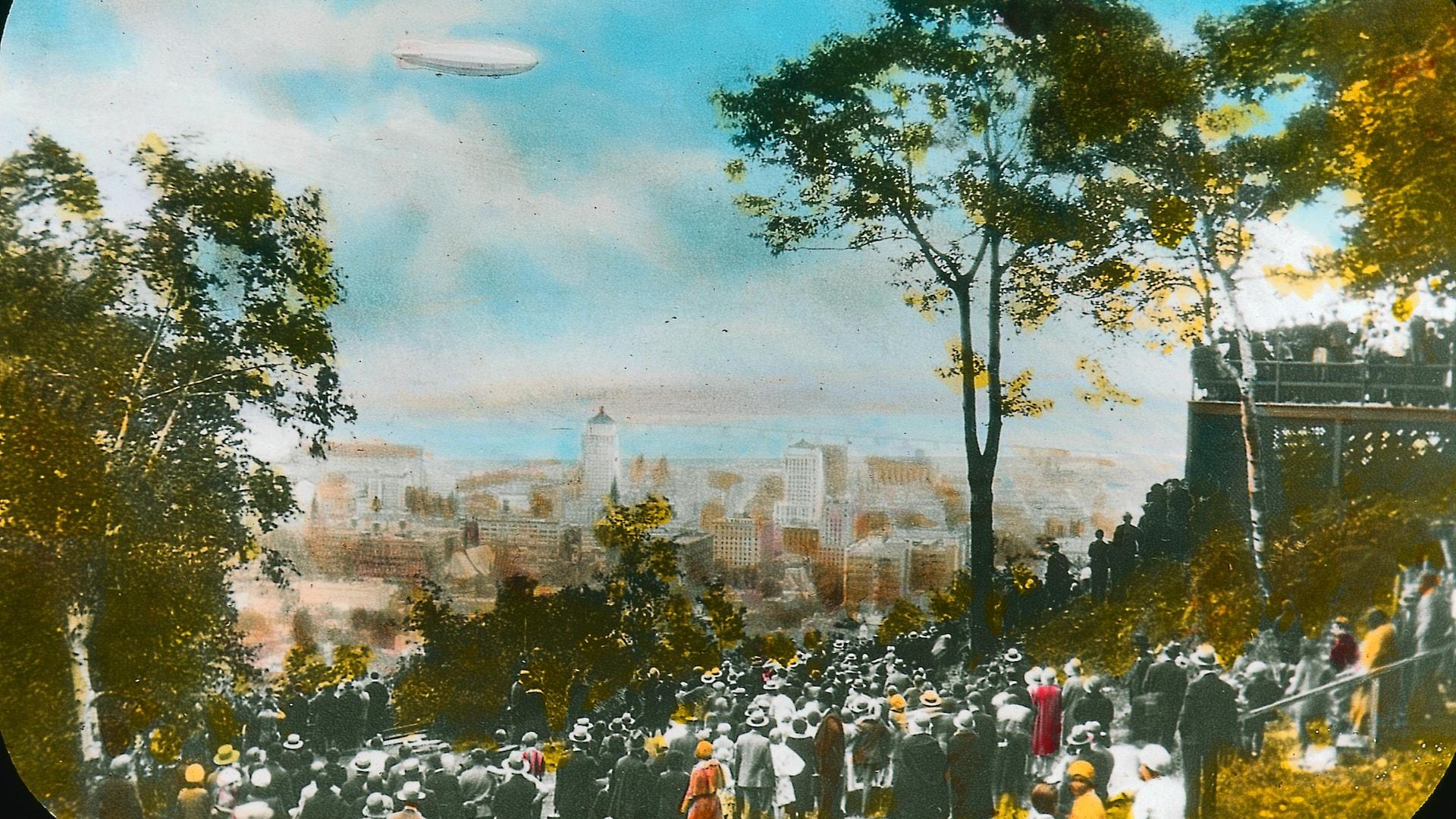 Le R-100 survole Montréal sous les yeux d'une foule massée sur les hauteurs du mont Royal, dans un ciel d'un bleu idéal. Des couleurs vives ont été ajoutées pour colorer la photo originale en noir et blanc.