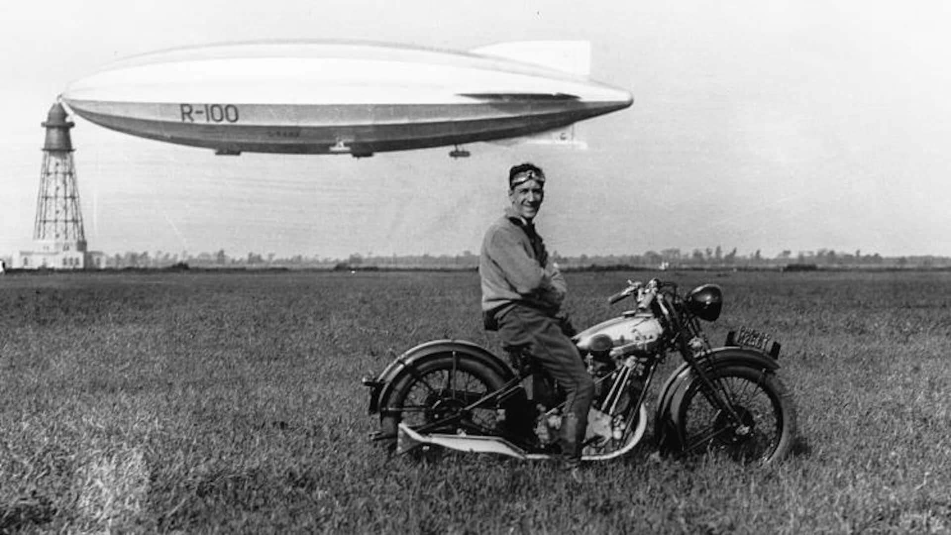 Un homme pose fièrement sur sa moto avec derrière lui le R-100 ancré à son mât.