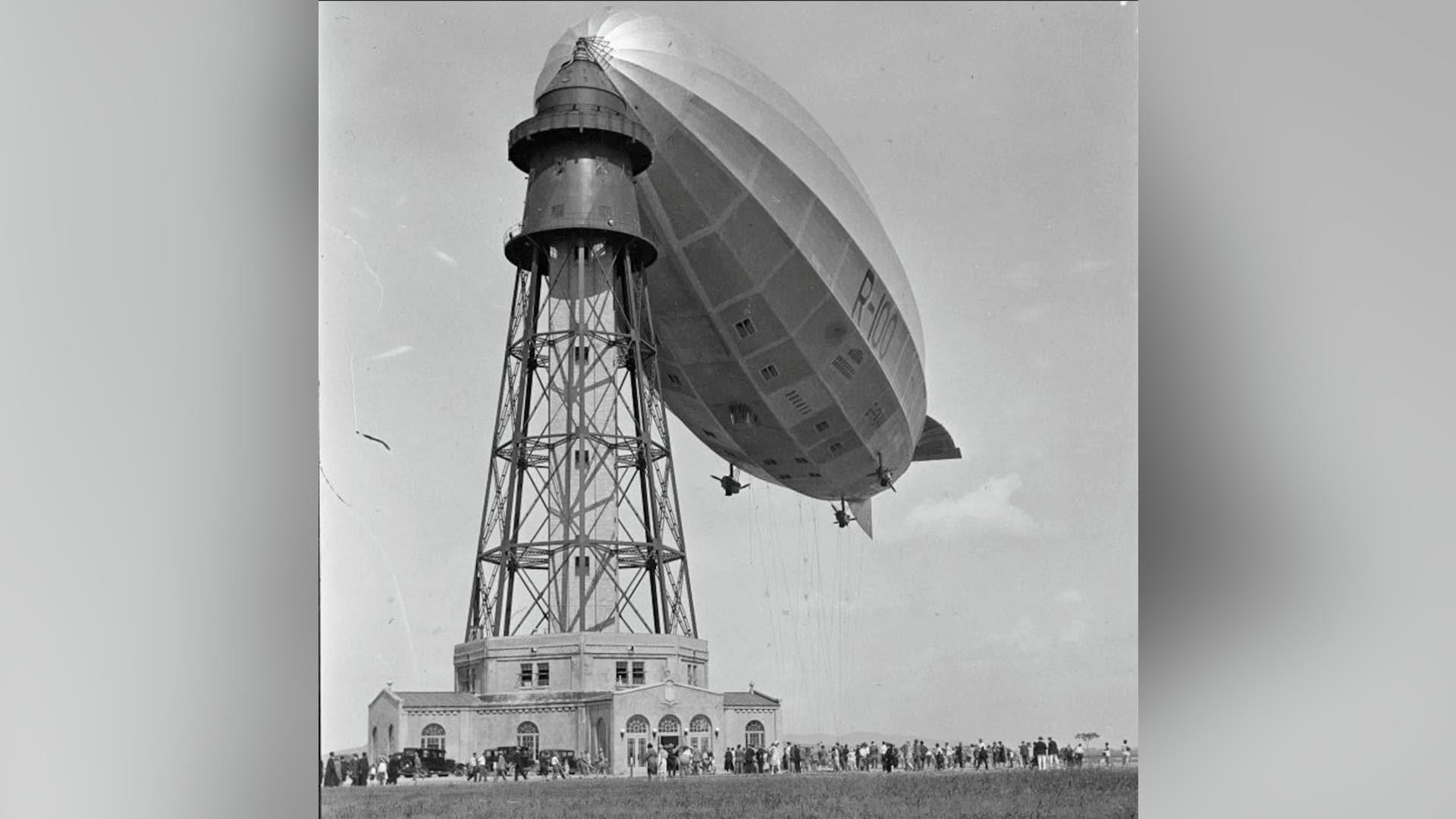 Une foule s'accumule sous le R-100 alors qu'il flotte sagement attaché à son mât, lors d'une belle journée d'été.