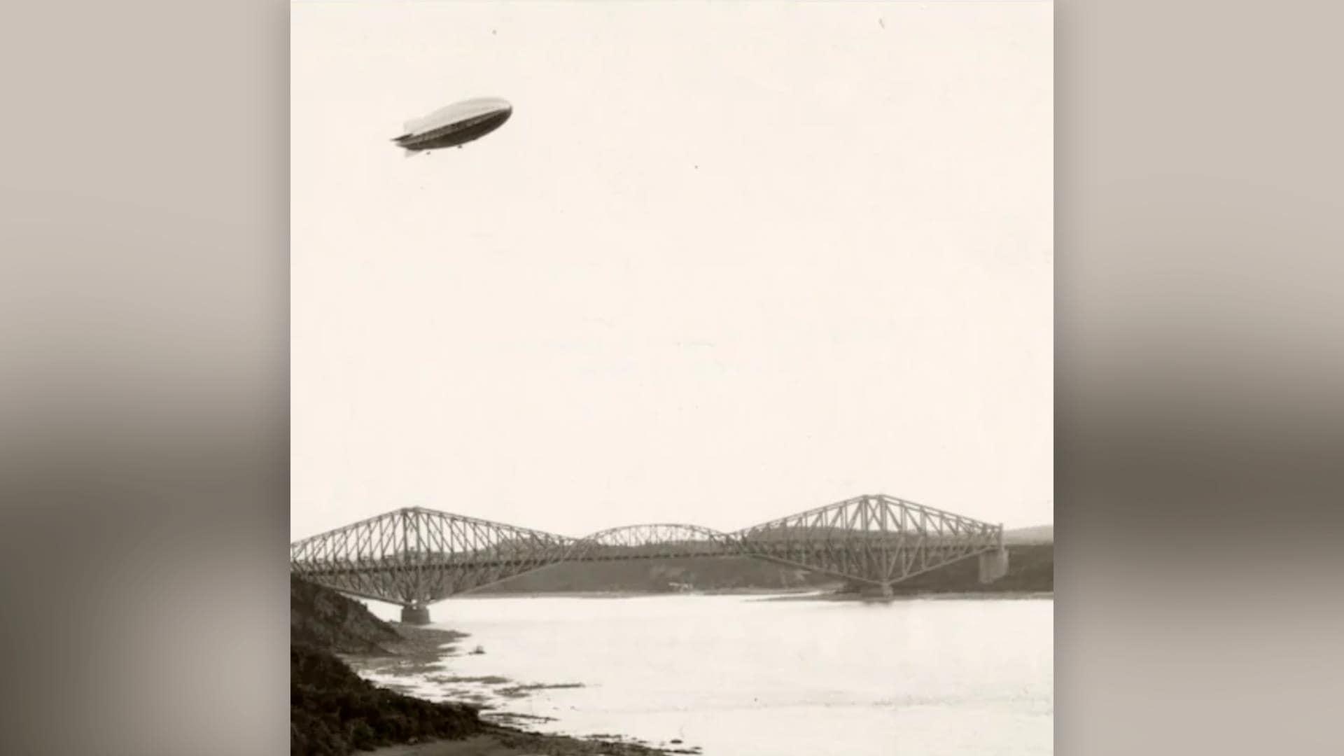 Le dirigeable R-100 passe au-dessus d'un pont de Québec apparemment désert, en route pour l'Angleterre.