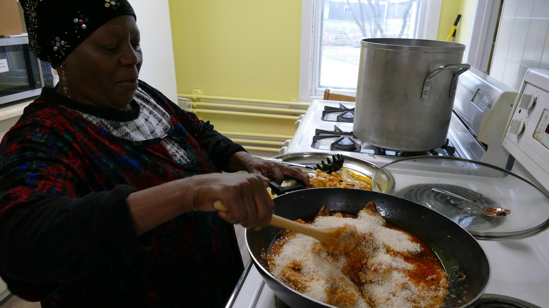 Une femme africaine mélange le riz concassé pour une recette de riz au gras.