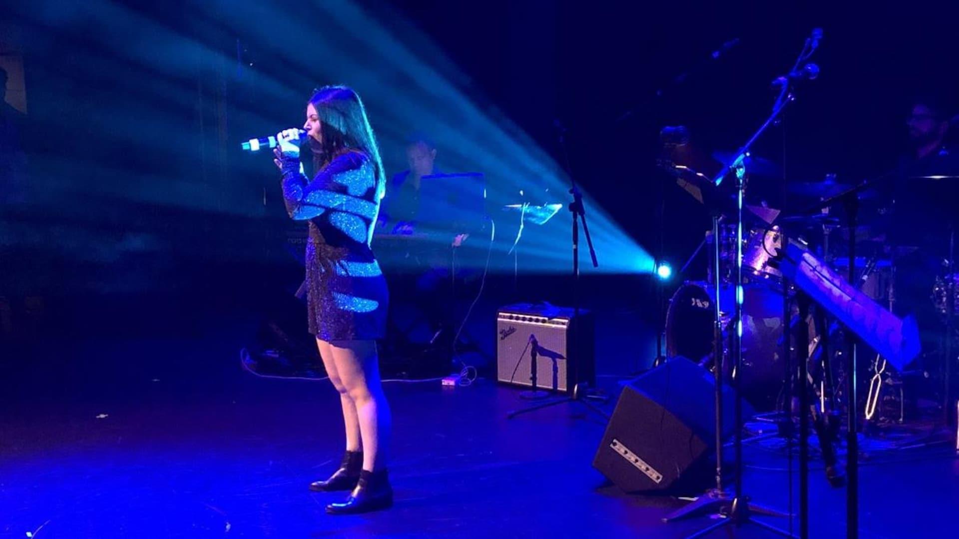 Une jeune fille sur scène un micro à la main.
