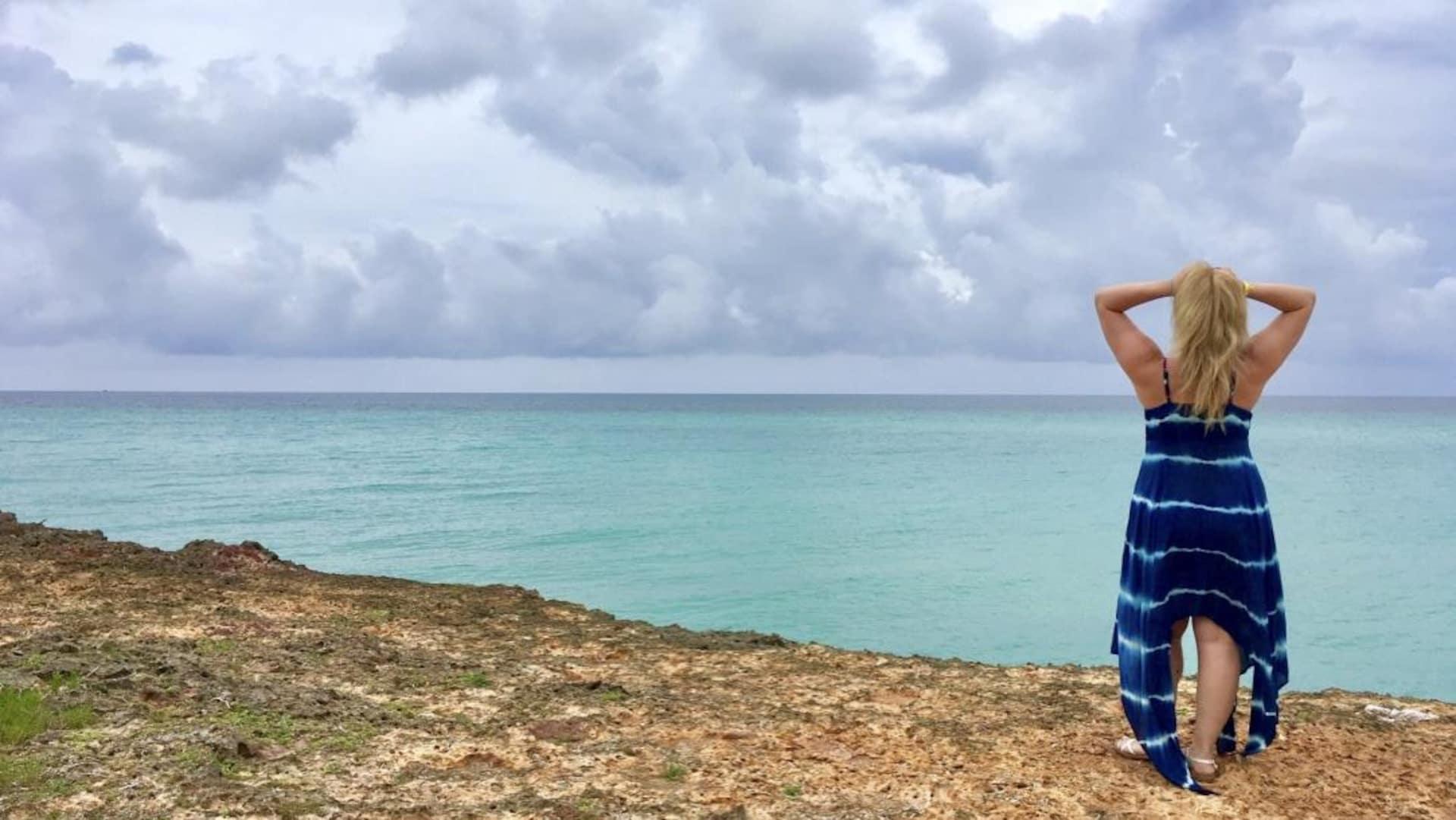 Une femme se tient debout de dos et regarde l'océan turquoise.