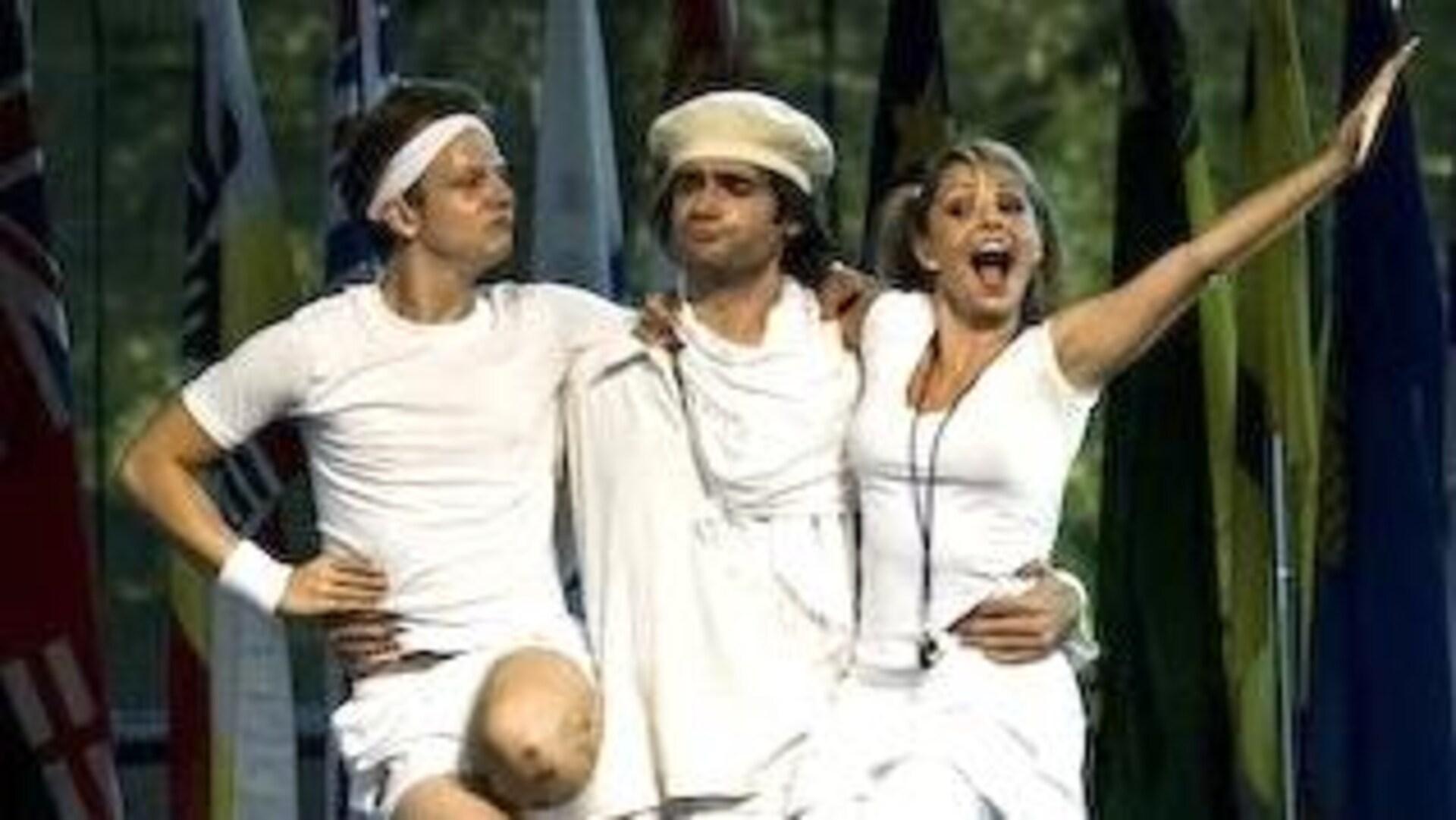 Trois personnes sont habillés en blanc sur une scène avec des drapeux en arrière d'eux.