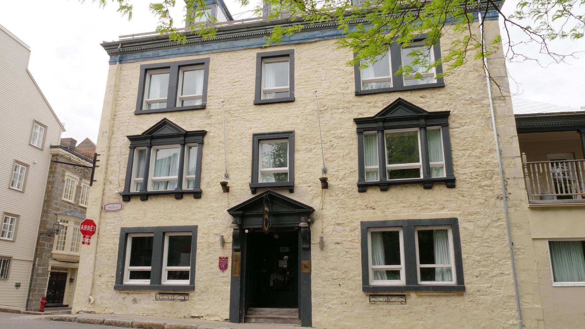 Une maison de pierre peinte couleur crème donne une jolie vue sur le parc voisin. Les larges fenêtres de l'étage et les trois lucarnes du toit lui donnent fière allure.