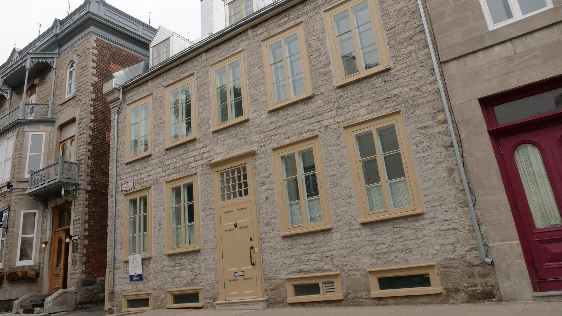 Une maison au toit de tôle à deux versants donne directement sur la rue. La porte rehaussée donne directement sur l'escalier à l'intérieur, elle est parfaitement alignée avec les fenêtres du rez-de-chaussée.