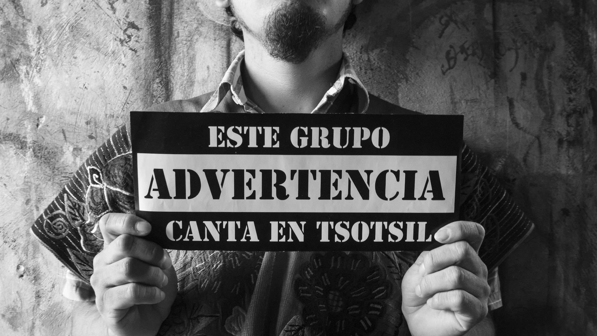 """Un membre du groupe tient une pancarte sur laquelle est écrit : """"Avertissement : ce groupe chante en tsotsil""""."""