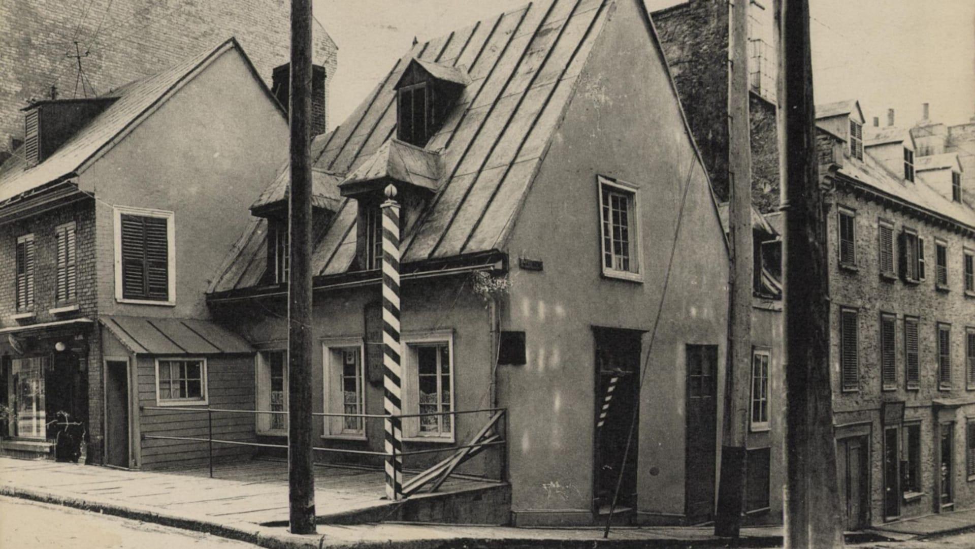 Le salon de barbier de Williams semble pimpant sur une image de 1908 utilisée comme carte postale, On voit des rideaux de dentelles aux fenêtres, et le mât de barbier semble repeint de frais, On voit aussi un à l'intérieur de l'entrée de côté, donnant sur la rue Desjardins.