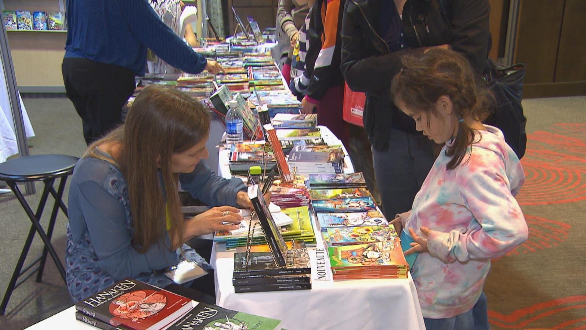 Une auteure signe un livre pour une jeune lectrice.