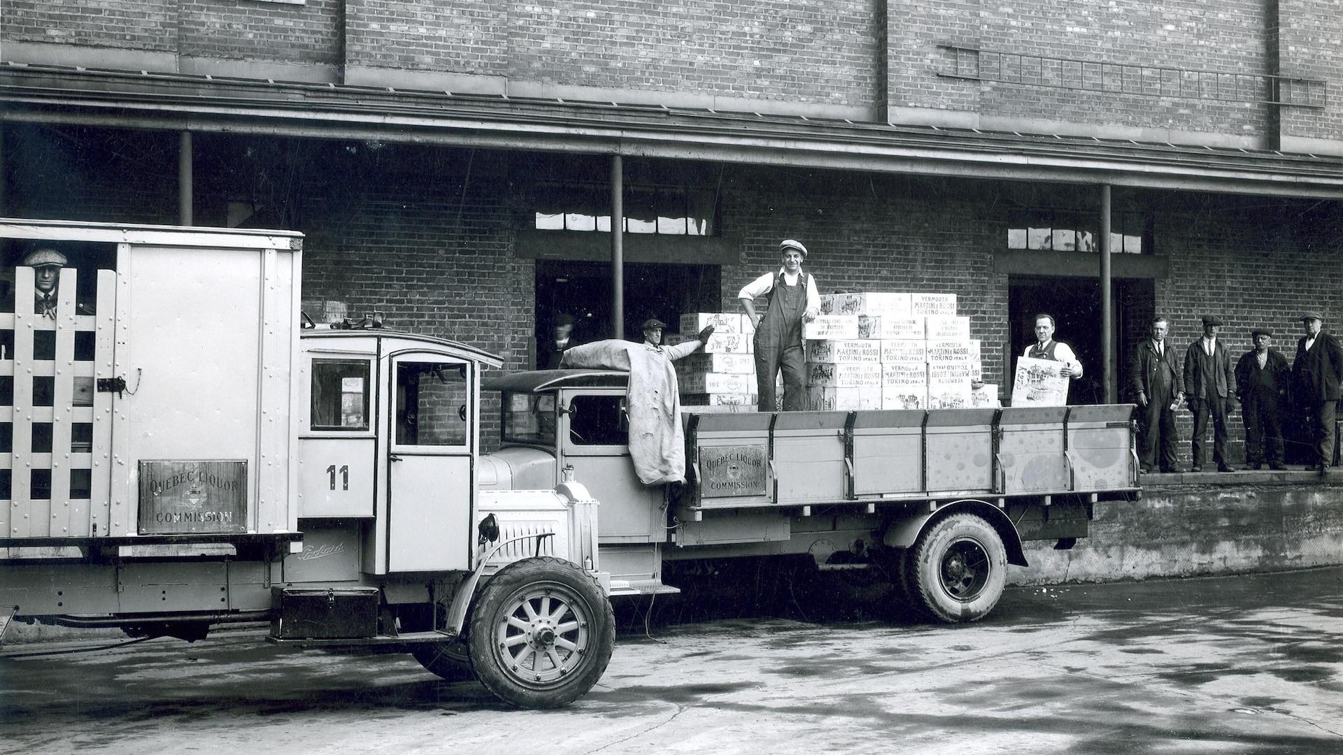 Des employés de la Commission des liqueurs sortent des caisses des entrepôts pour les charger dans les camions de livraison. L'un d'entre eux sourit à la caméra, pendant que d'autres surveillent des opérations à partir des quais.