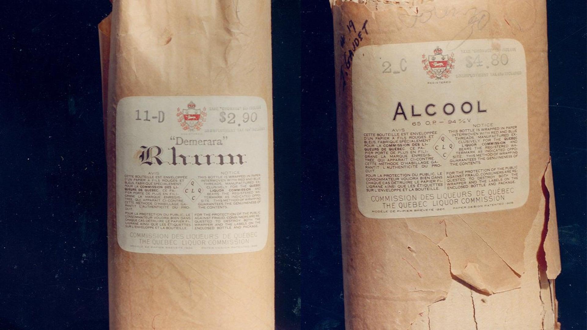 """Une bouteille de rhum et une autre indiquant """"alcool"""" avec leur emballage et les cachets de la Commission des liqueurs de Québec. On peut voir le prix, 2,90 pour le Rhum et 4,80 pour la bouteille d'alcool générique. On peut lire le nom du client sur l'emballage de la bouteille d'alcool: un certain M.Gaudet!"""