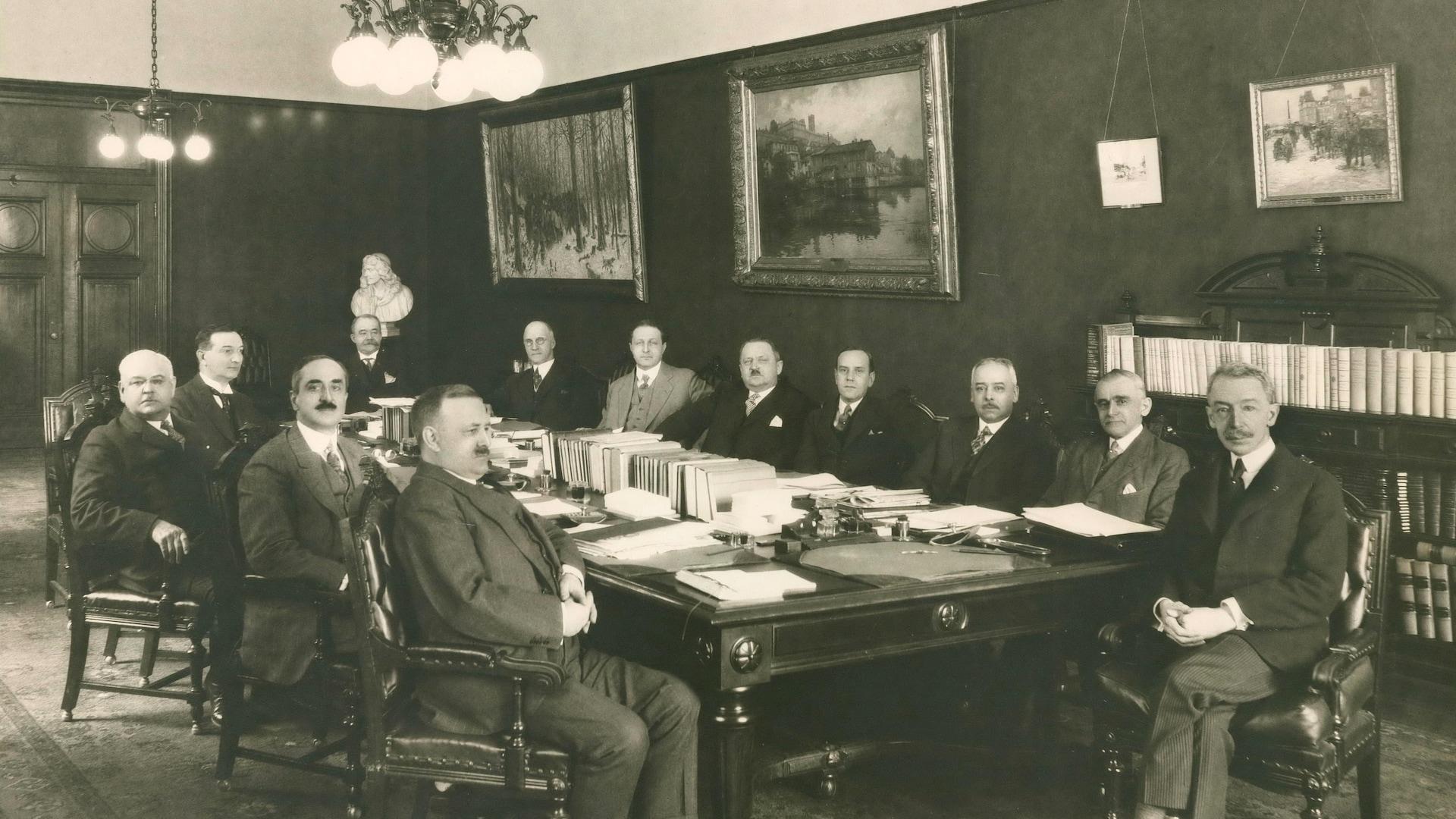Le premier ministre libéral Louis-Alexandre Taschereau avec son cabinet au tournant des années 1929-1930. Les hommes sont sérieux et regardent tous le photographe sans sourire, à l'exception d'un imposant monsieur moustachu, qui fait face au premier ministre.