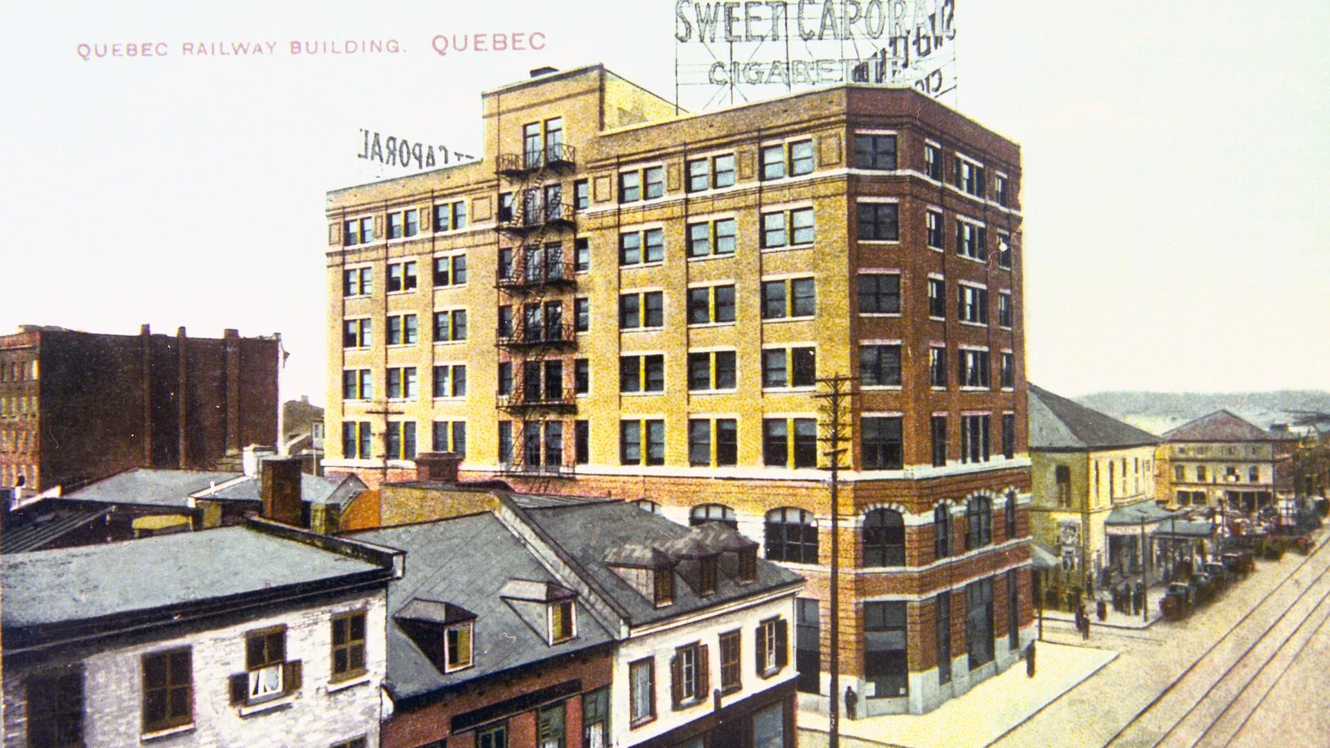 L'édifice de la Quebec Railway se trouve en plein centre-ville de Québec et domine la basse-ville depuis 1912. On voit les rails de tramway et des voitures, et l'édifice est dominé par une annonce de cigarettes Sweet Caporal.