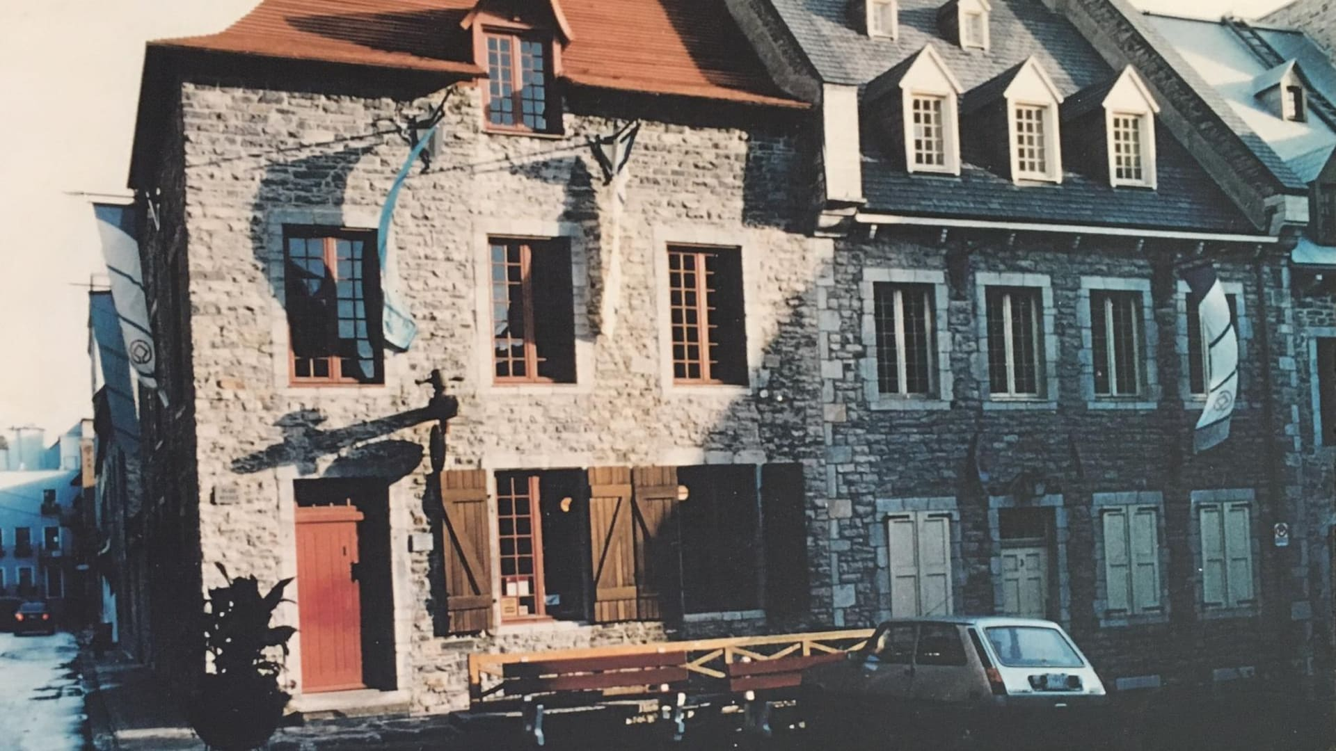 Le jour se lève sur la Maison des Vins de Québec, au début des années 1980, Une Renault 5, typique du temps, est stationnée juste devant les bancs publics près de l'entrée. Des caisses sont empilées à l'intérieur, derrière les fenêtres entrouvertes.