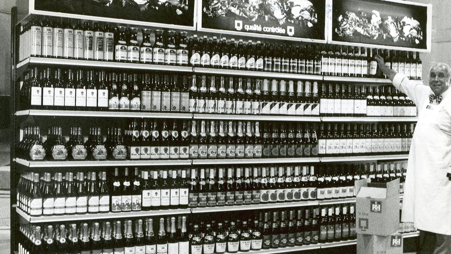 Un présentoir en usine, chargé de bouteilles de la SAQ. Un commis grisonnant et affable en tablier blanc et noeud papillon est en train d'aligner les dernières bouteilles sous l'oeil du photographe.