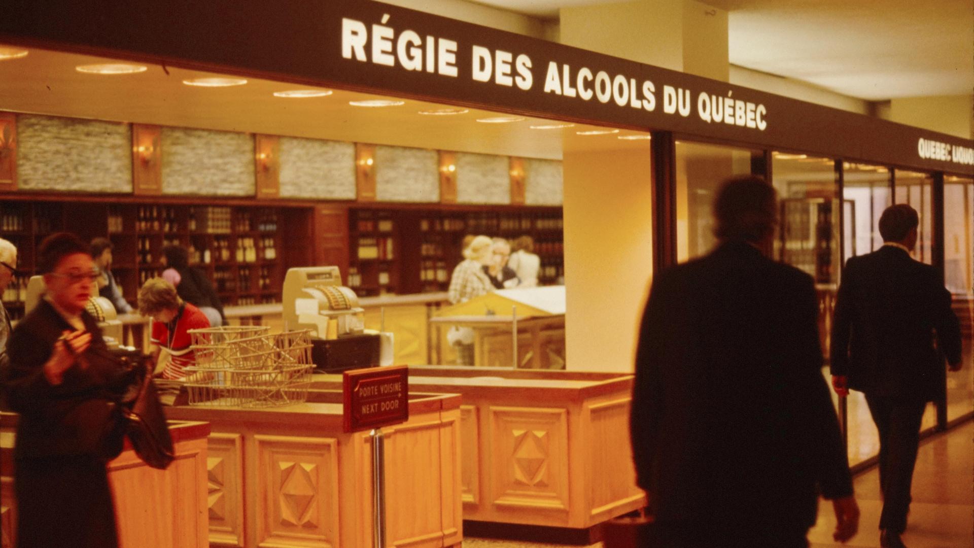 Une succursale de la Régie des alcools, durant les années 1960. Ce sont encore les employés qui ont accès aux bouteilles et qui peuvent les sélectionner pour les clients, même si les grilles d'autrefois ont disparu.