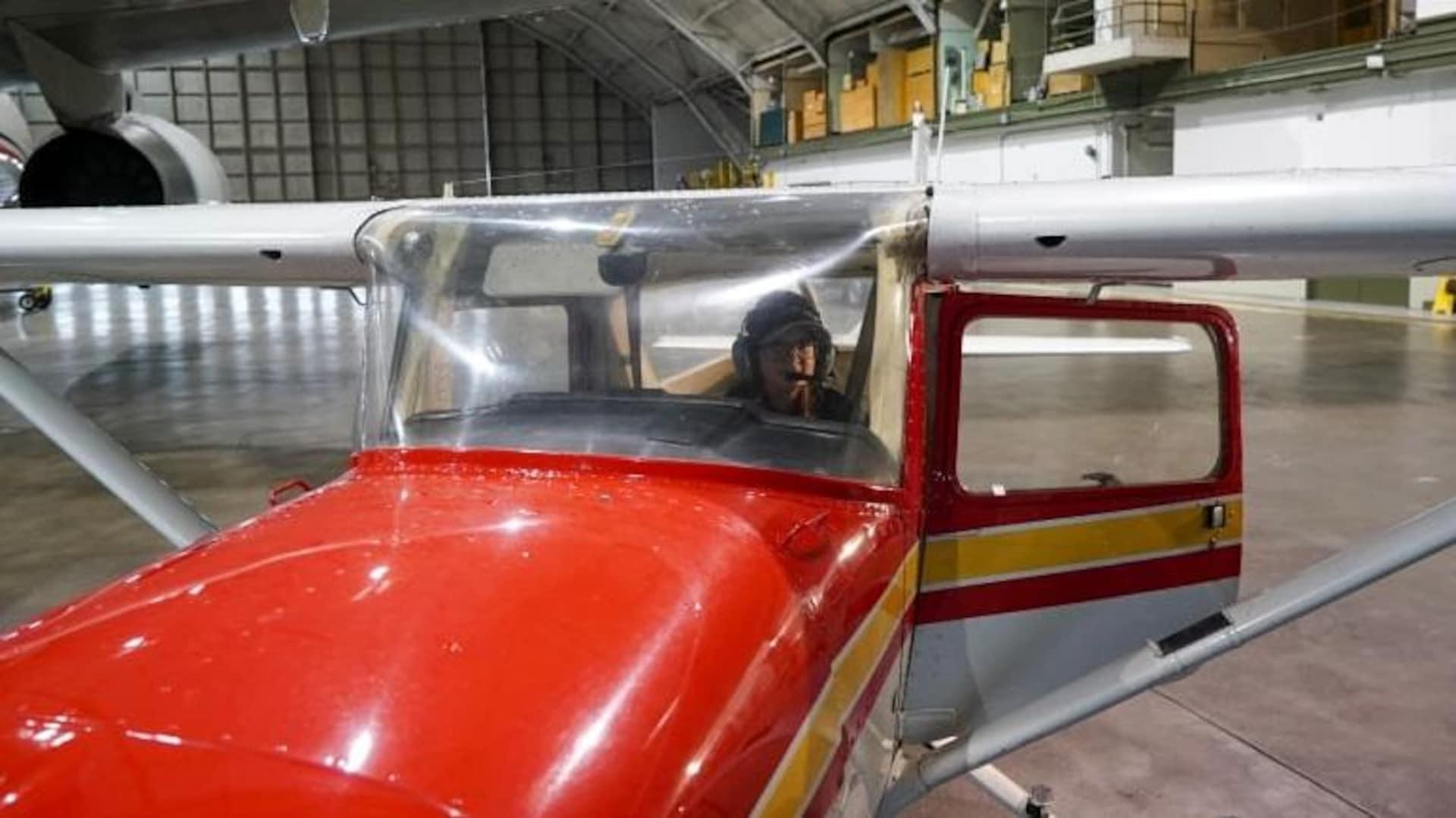 Sara Striker vue à travers le pare-brise d'un petit avion dans un hangar.