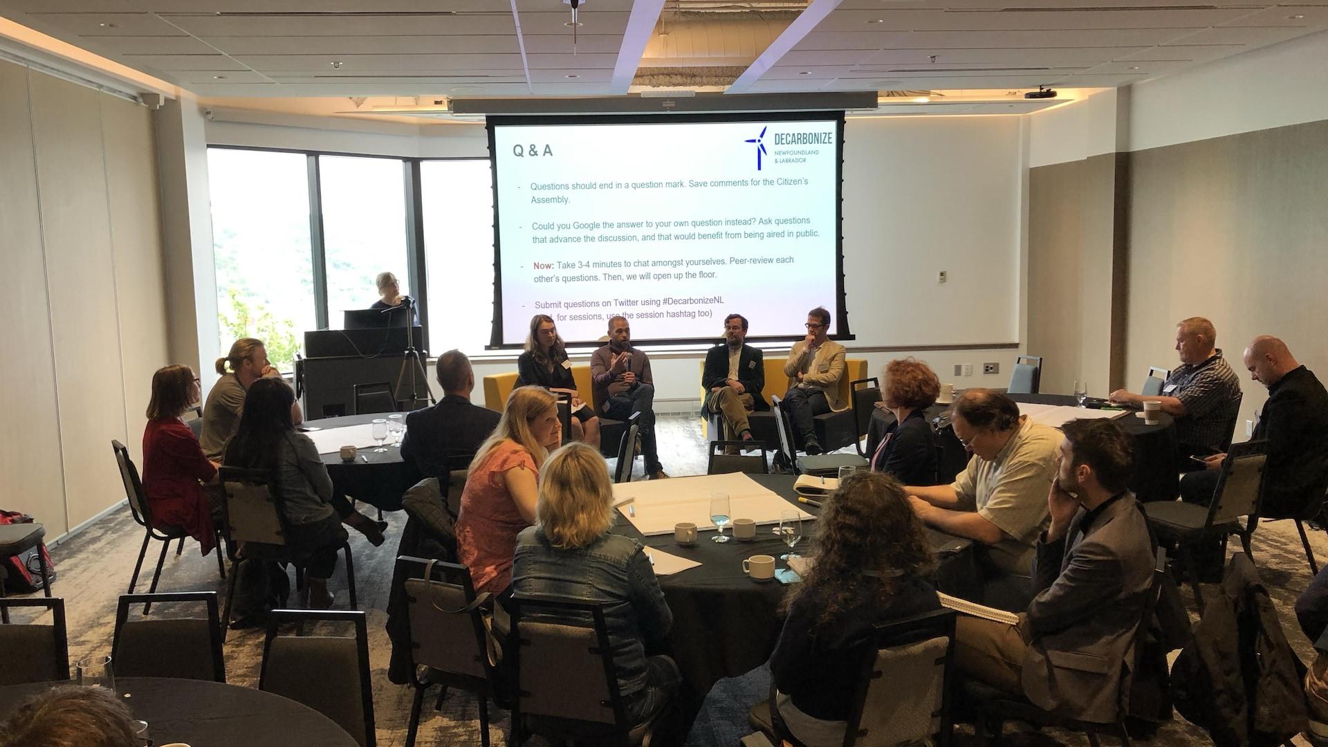 Des participants assis à des tables. Quatre personnes mènent la discussion au fond de la salle.