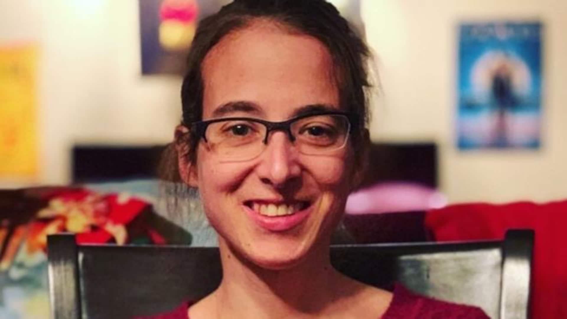 Portrait en couleur de l'autrice Sophie René de Cotret. Elle porte des lunettes et un chandail rouge.