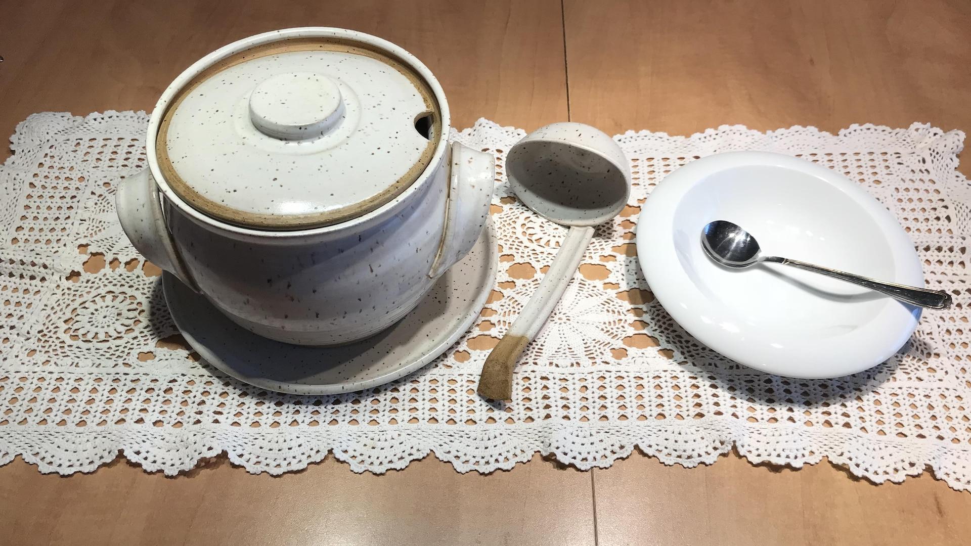 Sur la table, une soupière avec sa louche et un plat à soupe
