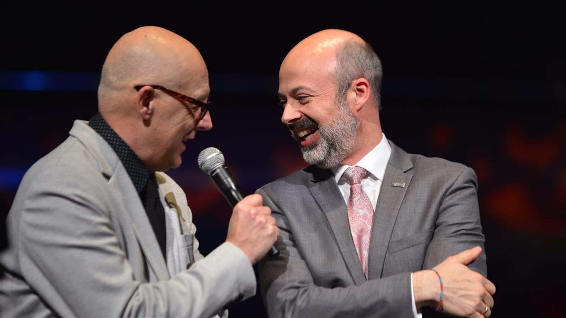 Deux hommes qui discutent à l'avant-scène.