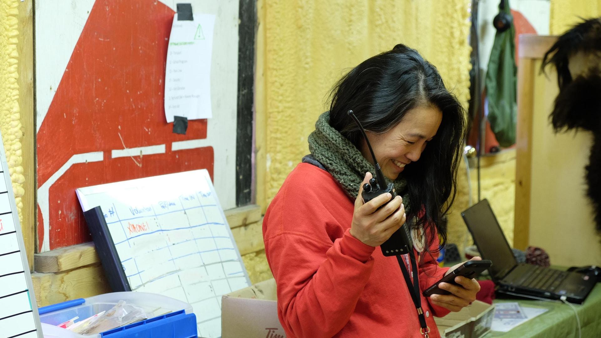 Une femme souriant tenant une radio et un téléphone.