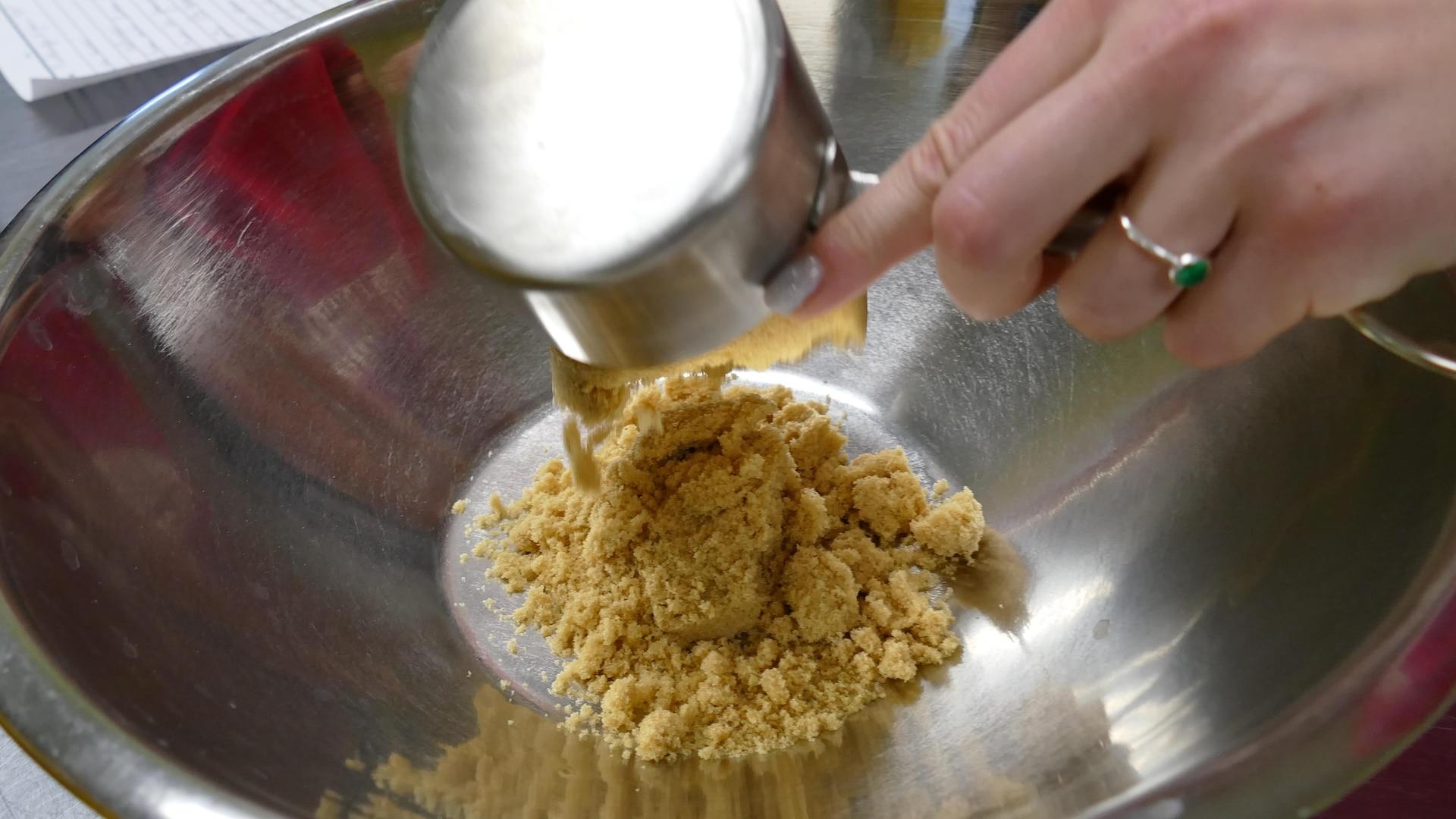 À l'aide d'une tasse à mesurer en métal, une main verse dans un grand plat le sucre brun.