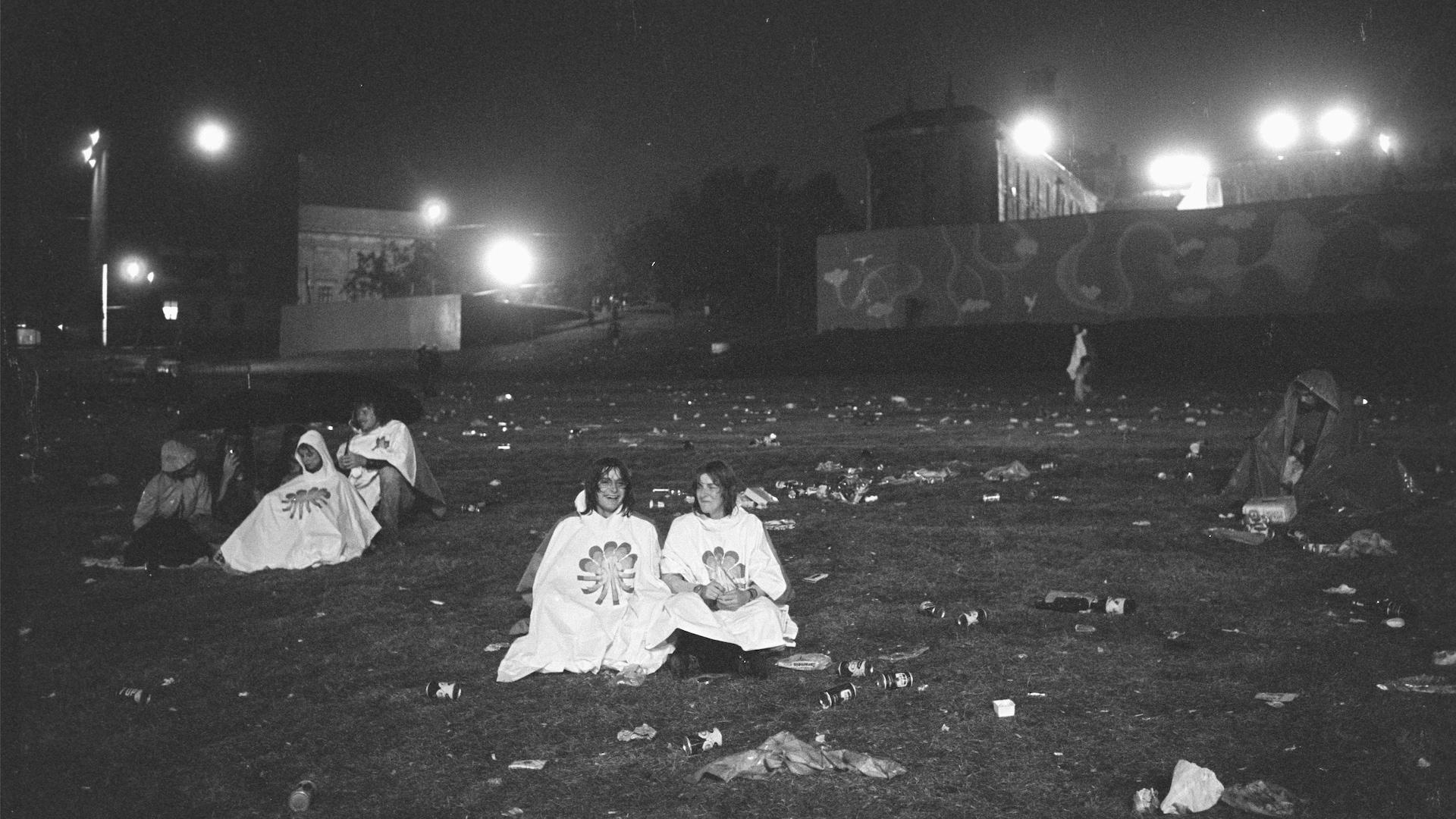 Des festivaliers assis sur le terrain presque désert et jonché de détritus se font mouiller après le spectacle, et ils ont l'air de trouver ça très drôle!