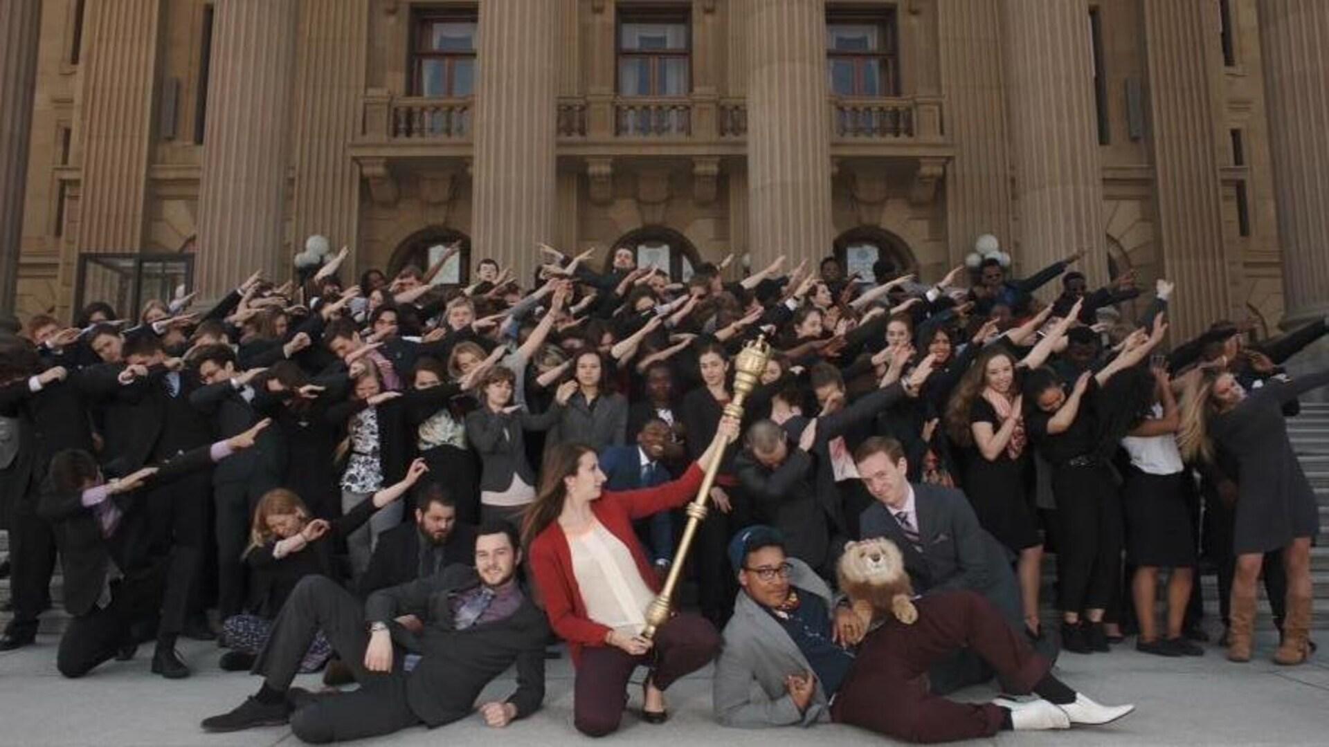 Plusieurs jeunes sont devant le parlement et lèvent les bras vers leur gauche.