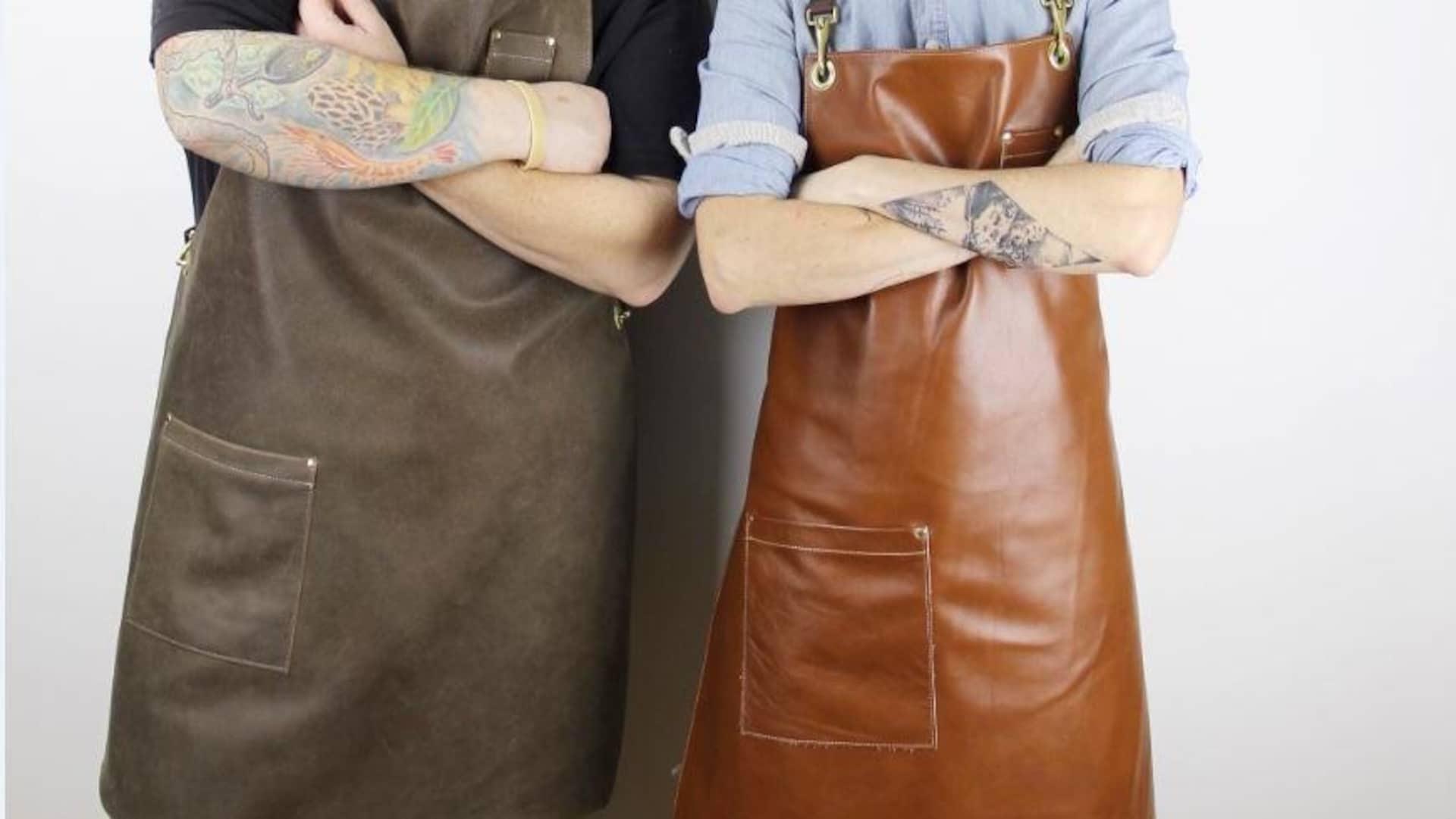 Deux personnes se tiennent debout et portent des tabliers en cuir dans les tons de bruns.