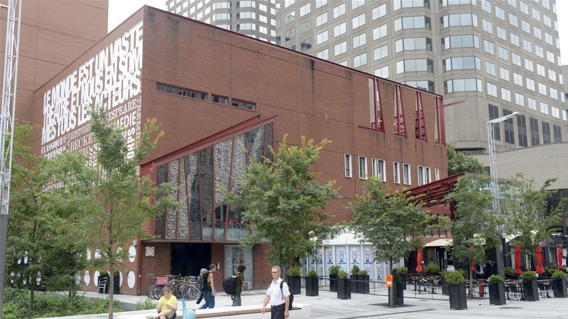 Des passants marchent devant le Théâtre du Nouveau Monde à Montréal.
