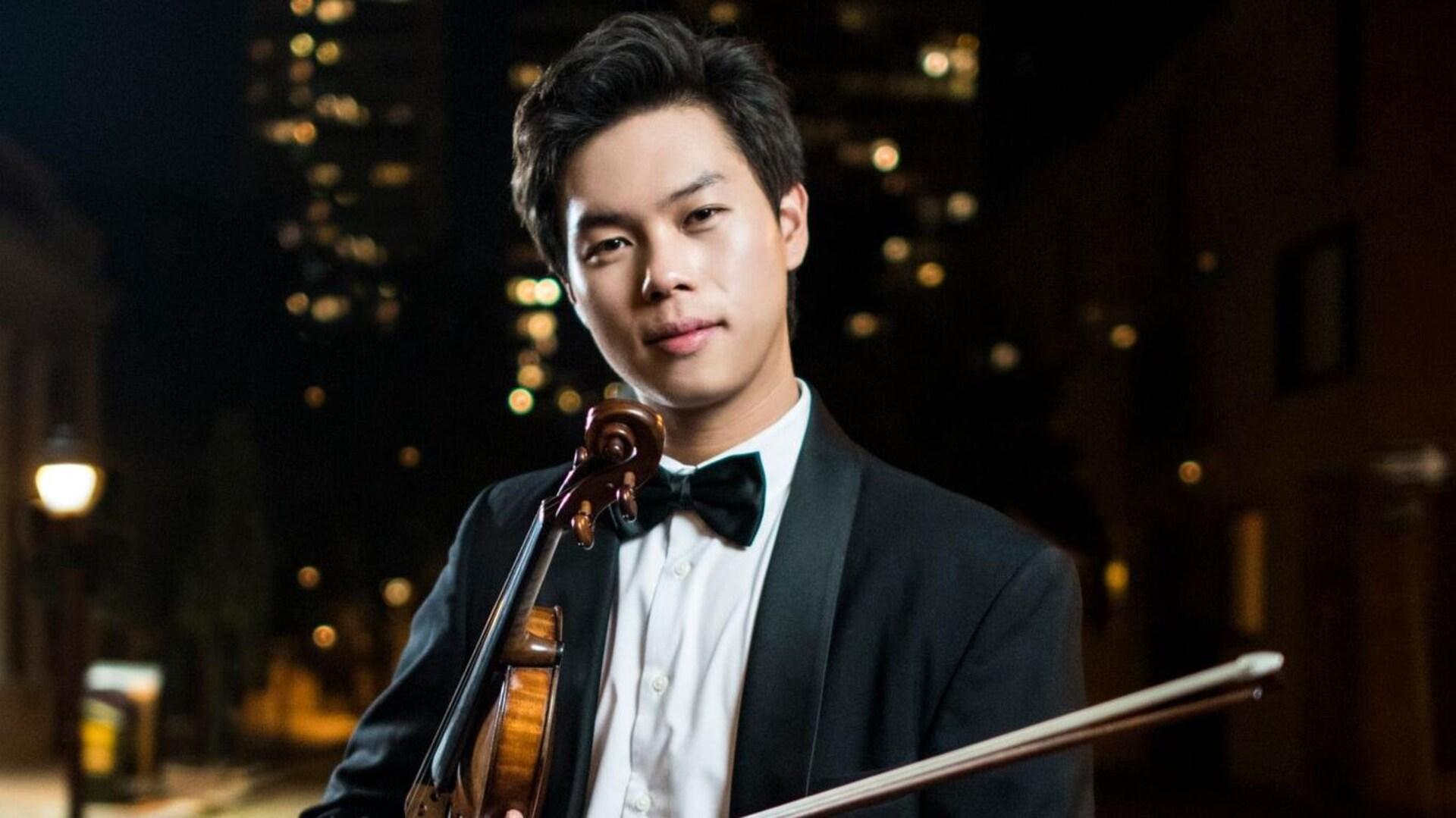 Un jeune garçon en veston avec un noeud papillon avec son violon, le soir, dans la rue.