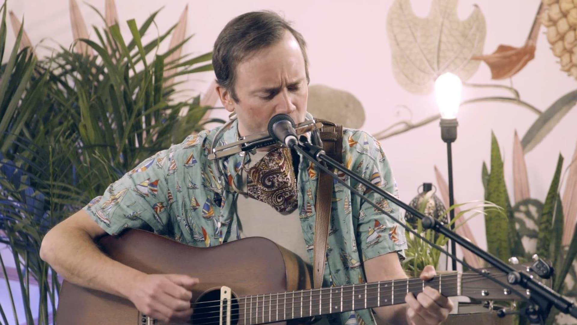 Le musicien Tom Keenan souffle dans un harmonica en jouant de la guitare.