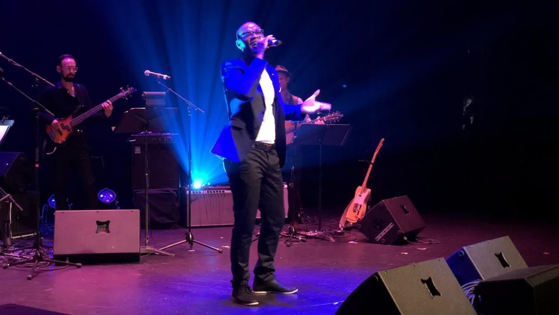 Un homme chante sur scène, un micro à la main.