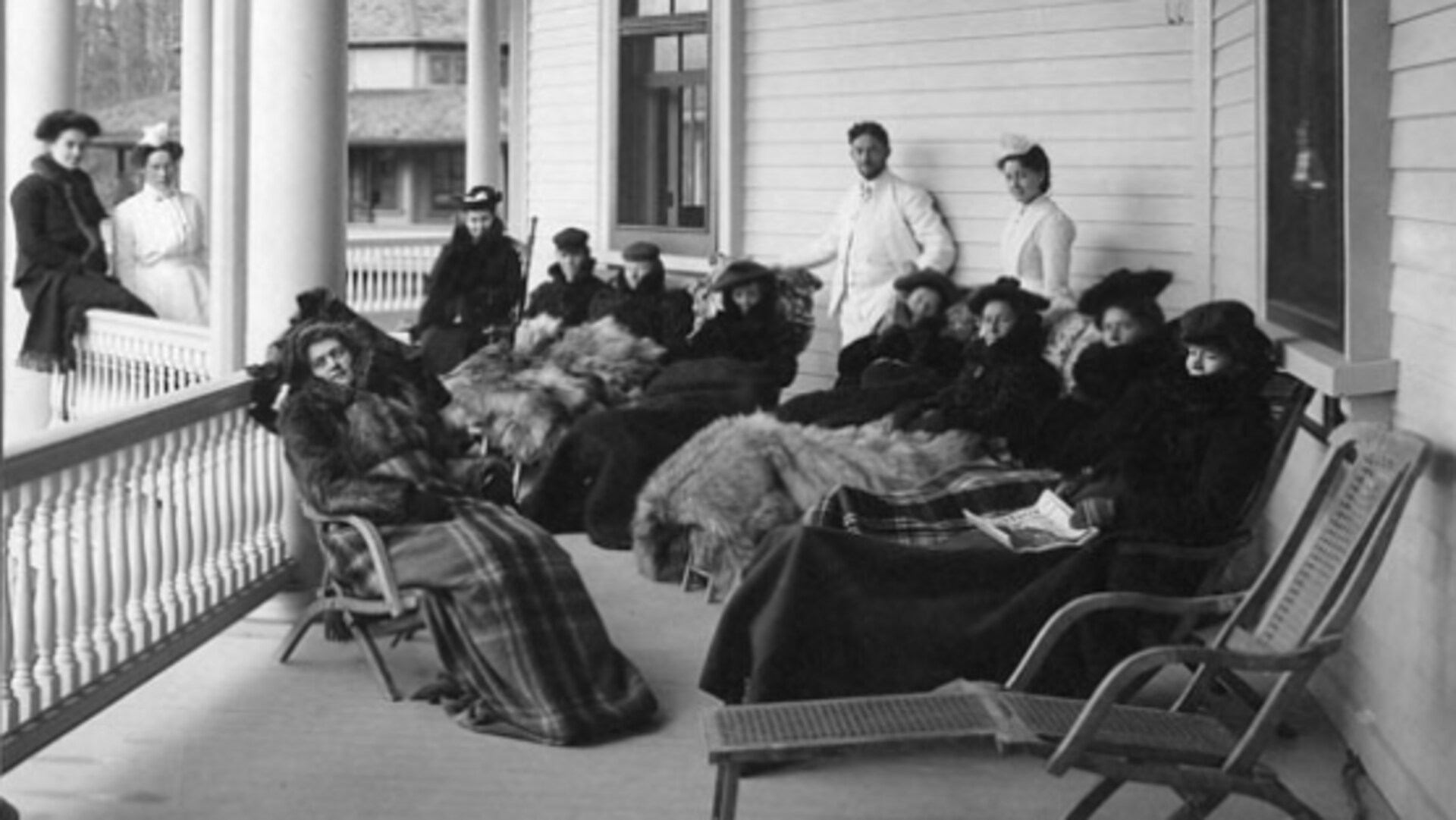Des patients en cure soigneusement emmitouflés dans de luxueuses fourrures prennent de l'air sur la galerie d'un vaste cottage.