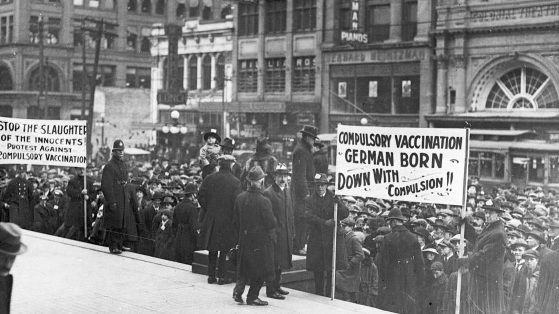 Une foule anti-vaccin brandit des pancartes et manifeste devant l'Hôtel de Ville de Toronto dans les années 1930.