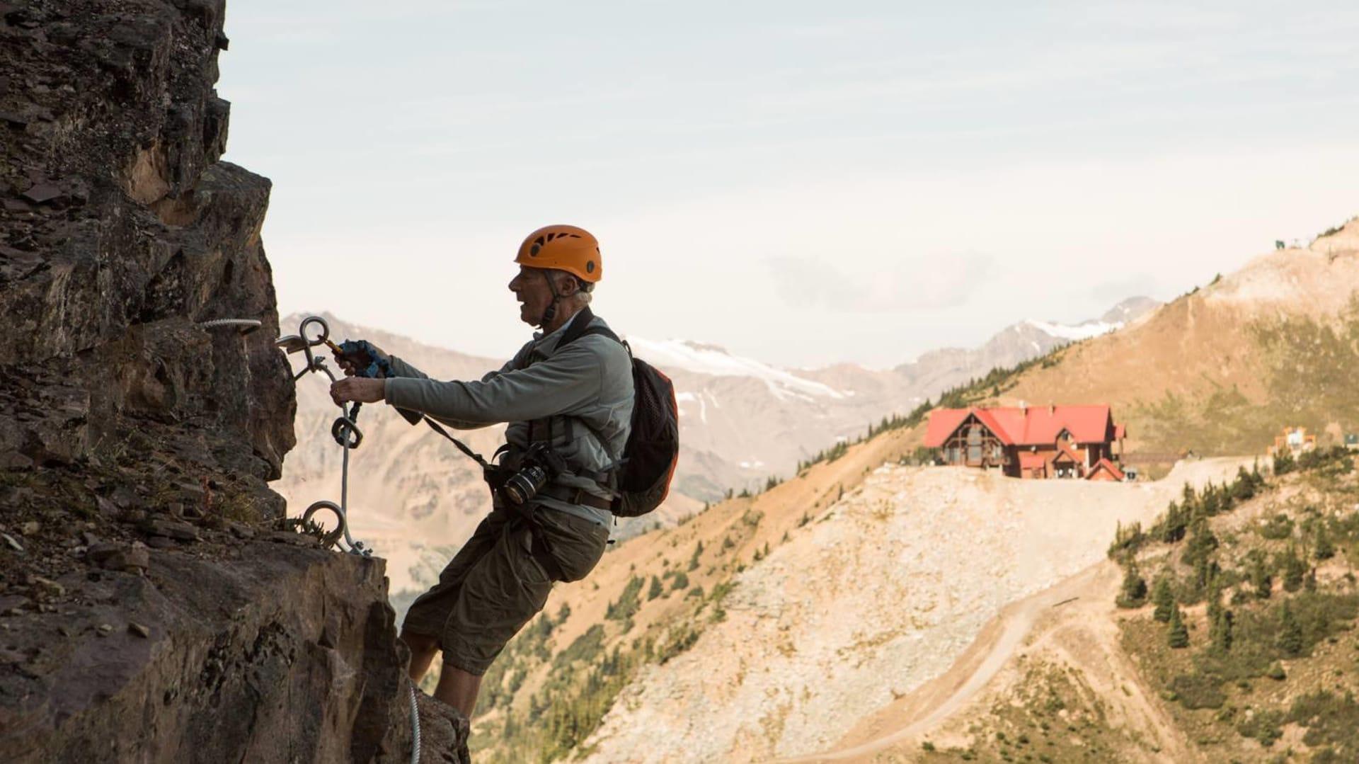 Un homme escalade une paroi rocheuse. En arrière-plan, les montagnes Rocheuses.