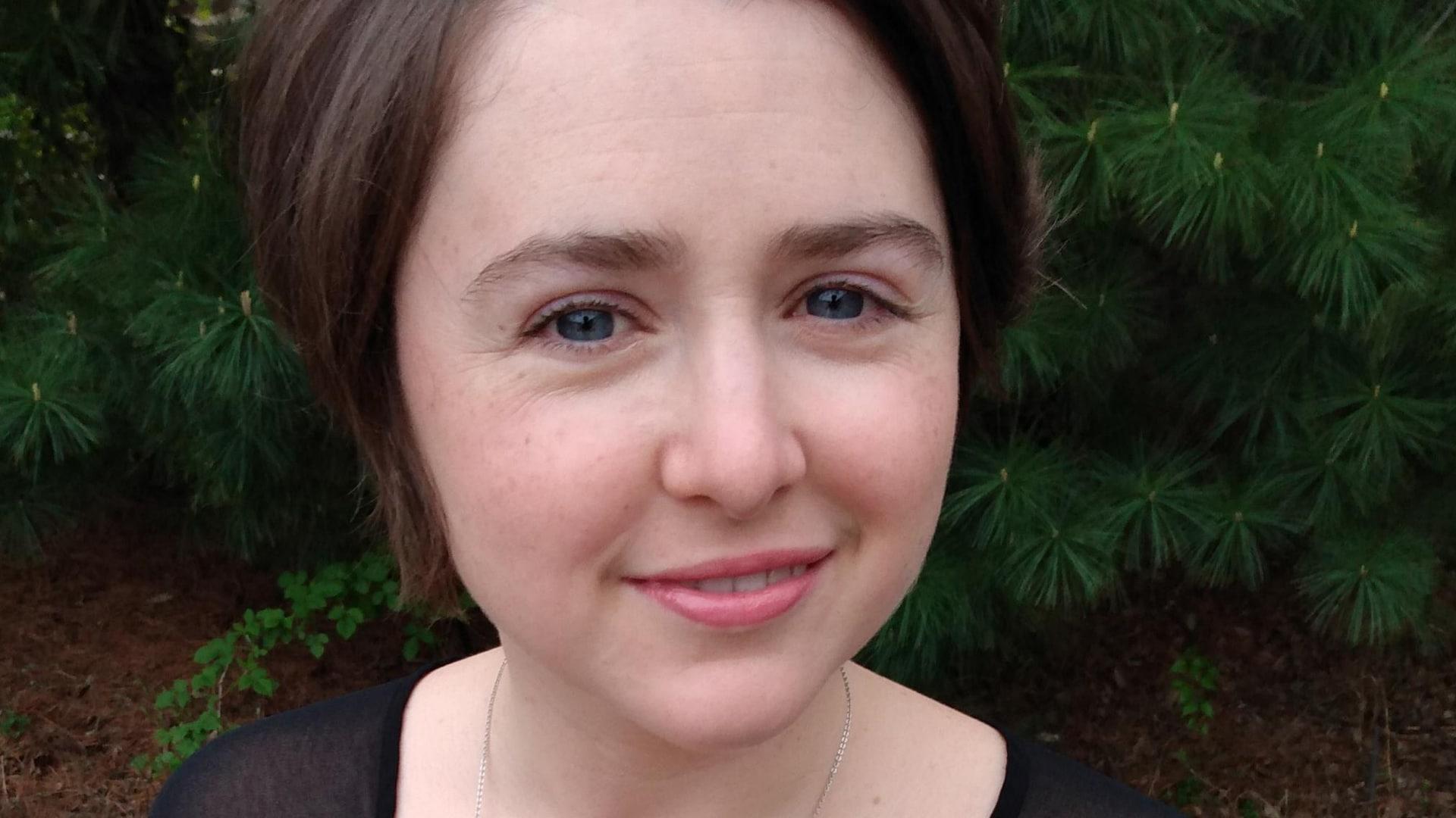 Portrait en couleur, en extérieur, légèrement en plongée de l'autrice Vicky Larochelle. Elle porte un haut noir à manches courtes et une chaîne autour du cou. En arrière-plan : des pavés et des branches de conifère.