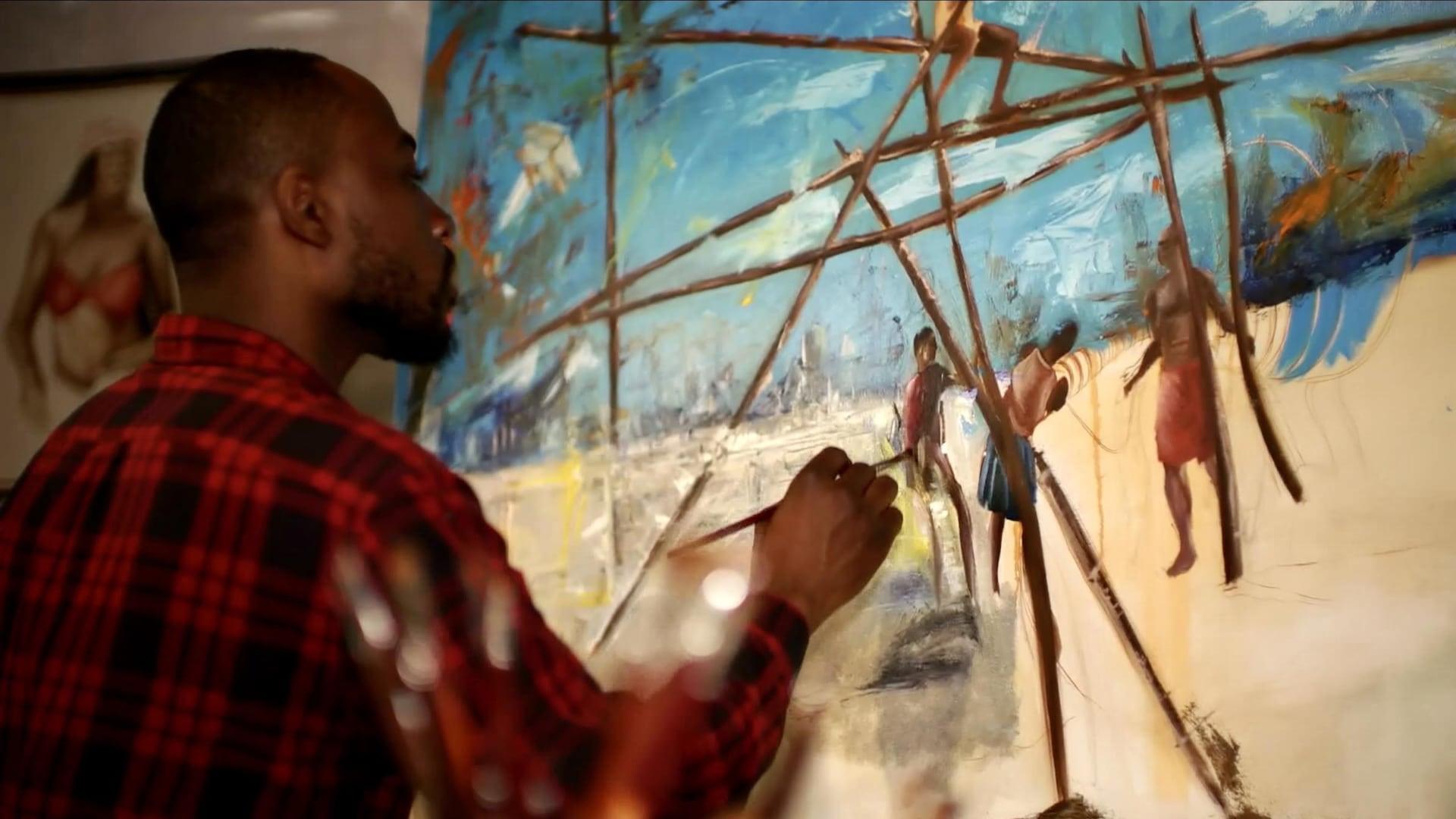 L'artiste Xavier Mutshipayi peignant un tableau, dans son atelier.