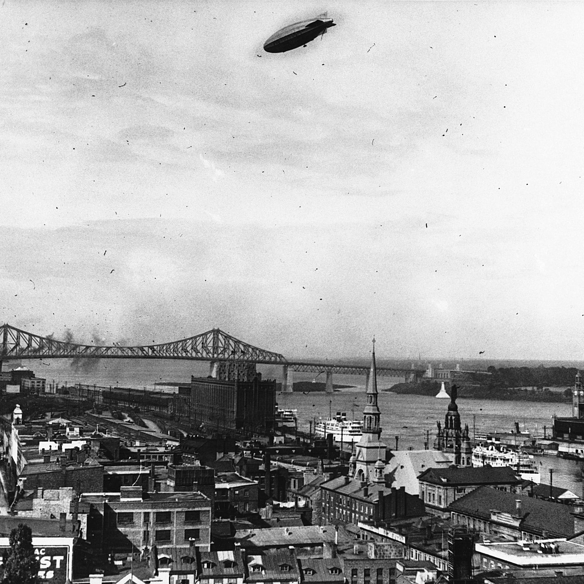 Le R-100 semble petit dans le ciel de Montréal, qui se déploie dessous, avec en arrière-plan le pont Jacques-Cartier.
