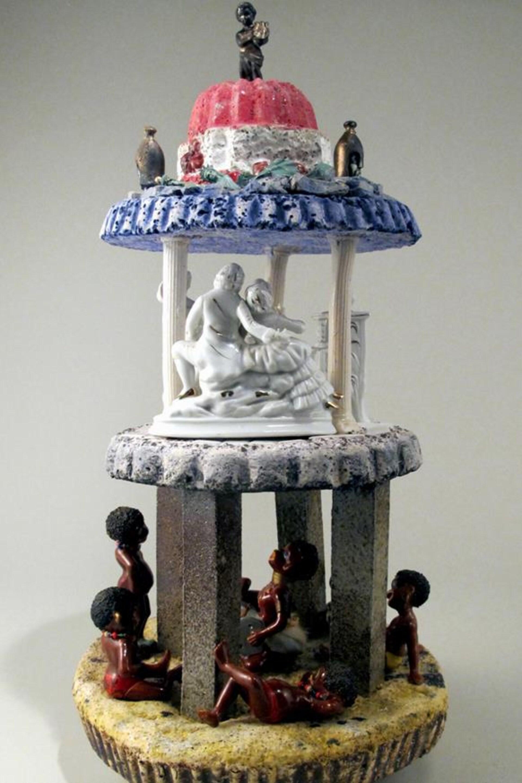 L'oeuvre du céramiste fransaskois Charley Farrero intitulée Americana. Il y a une tour à plusieurs étages. En bas il y a des figurines de personnages noirs et en haut il y a des figurines de personnages blancs.