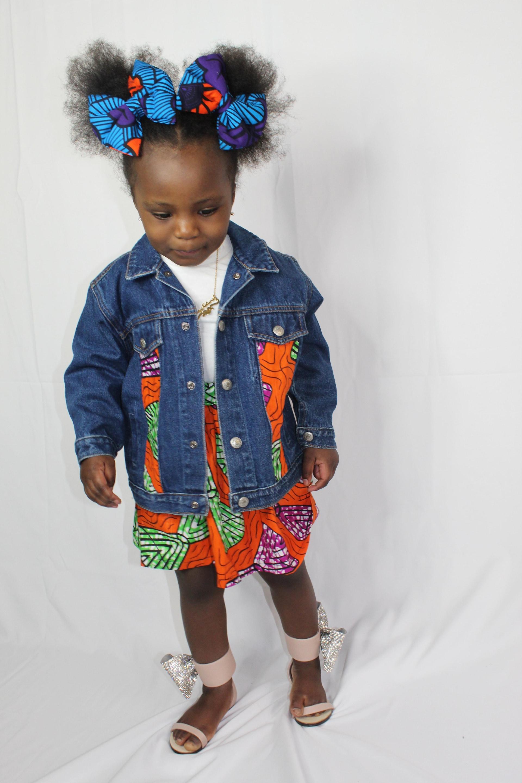Un enfant porte un veston en denim sur lequel on a ajouté des morceaux de tissu de pagne, un processus que l'on appelle surcyclage.