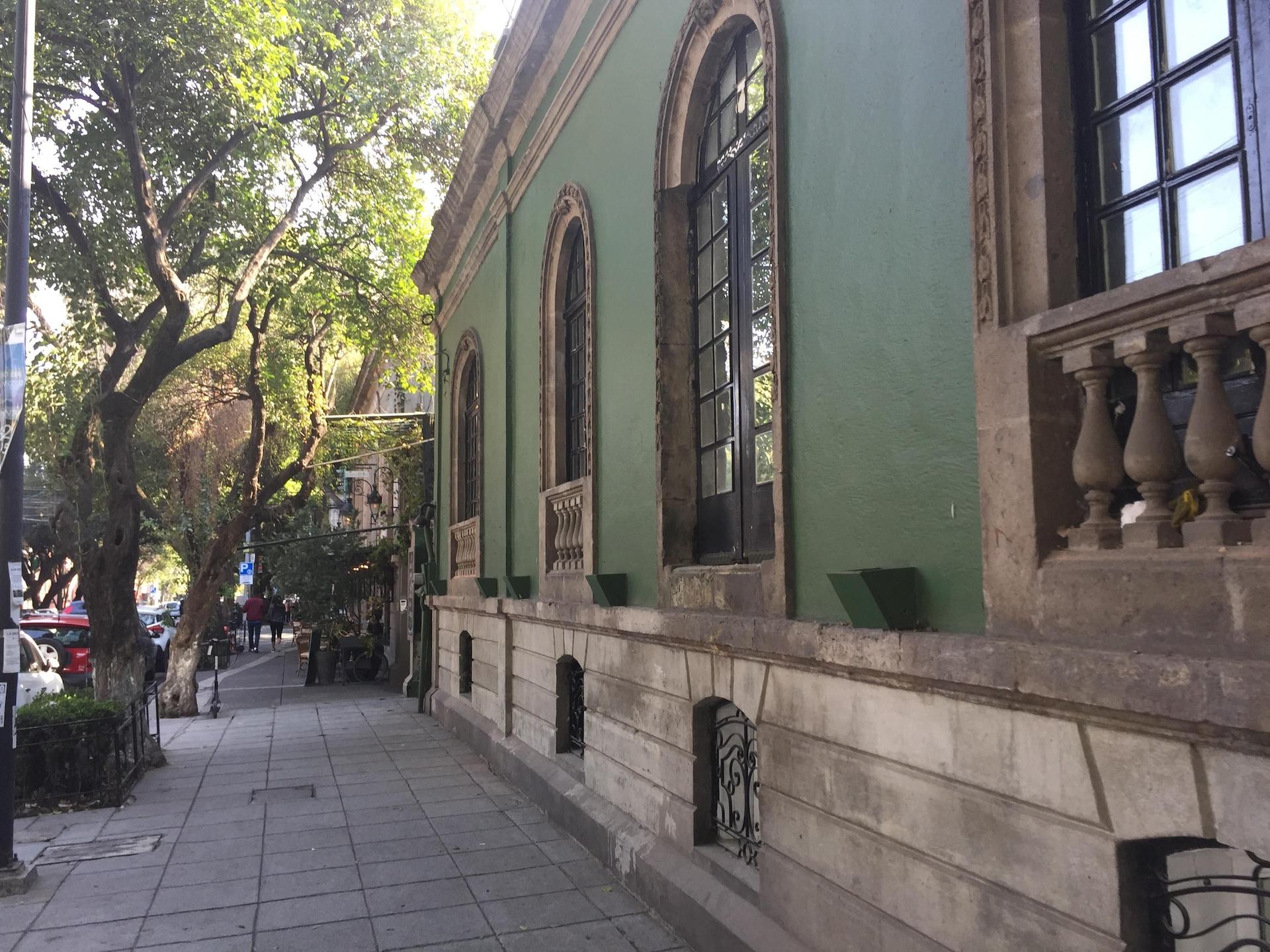 Un trottoir pavé large et bordé d'arbres, et un bel immeuble.